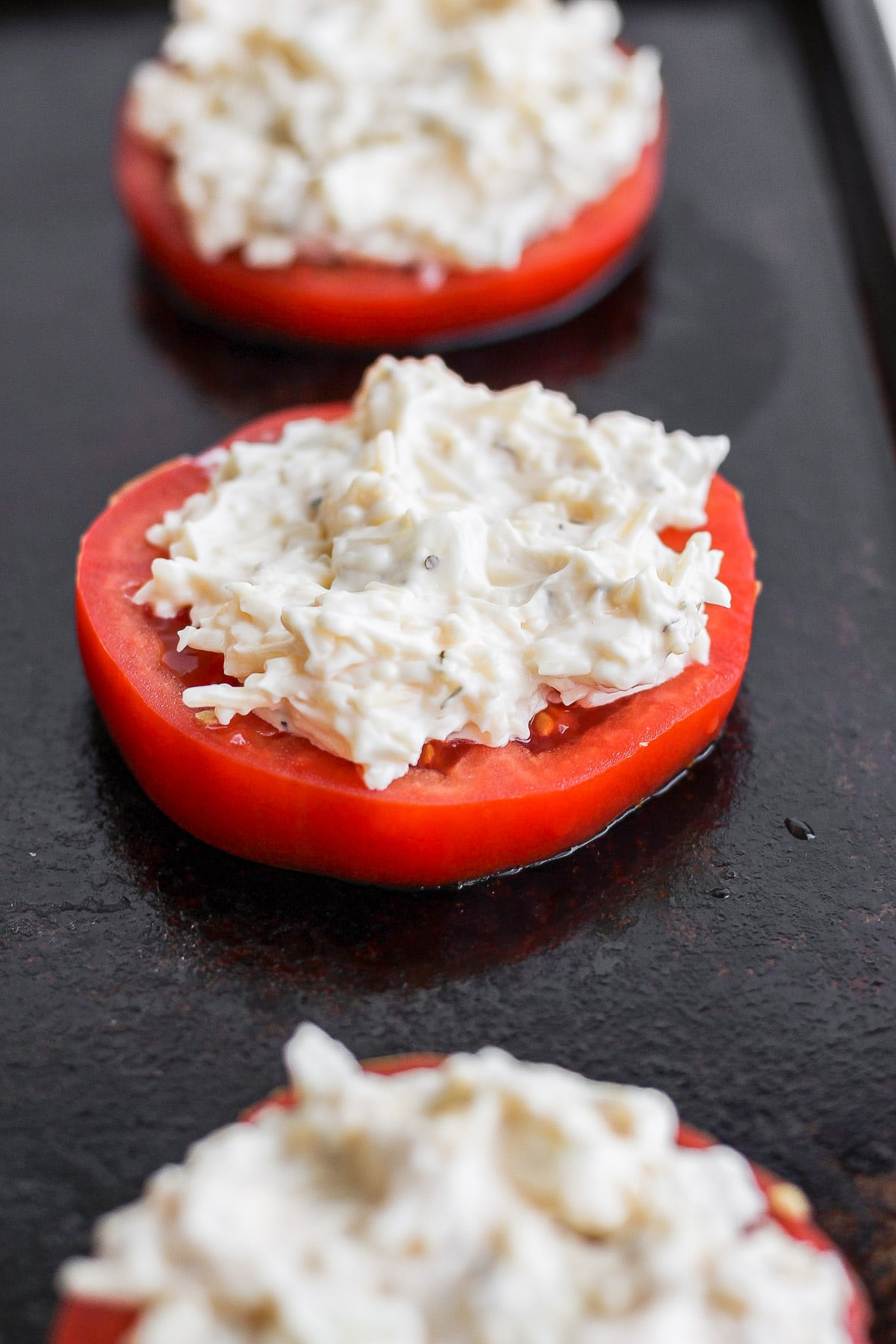 Sliced tomatoes with a mayo parmesan mixture on top.
