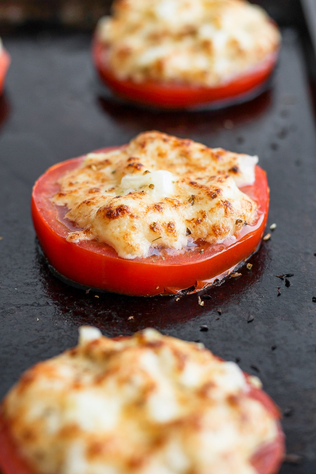 Thick sliced tomatoes with a mayo parmesan mixture on top that is browned from the broiler.