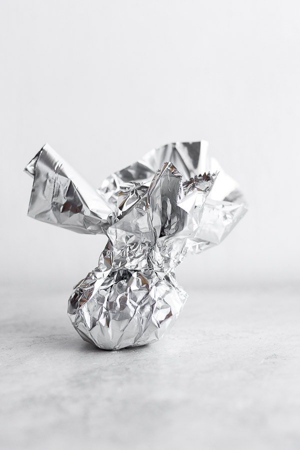 Showing how you can wrap up garlic with foil.