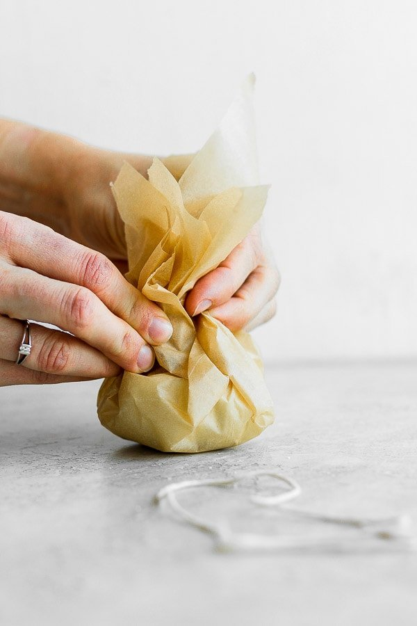 Showing how to wrap garlic in parchment paper.