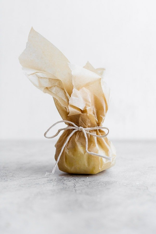 Roasted garlic tied up in parchment paper.