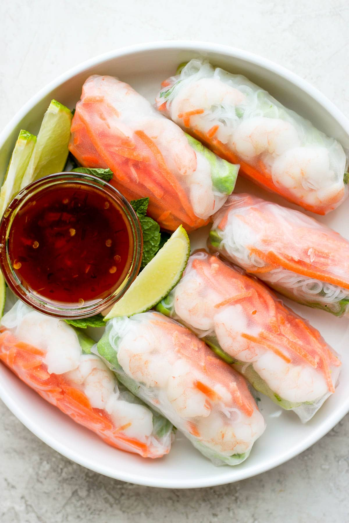 Bowl of shrimp spring rolls with a smaller bowl of dipping sauce and a few lime slices.
