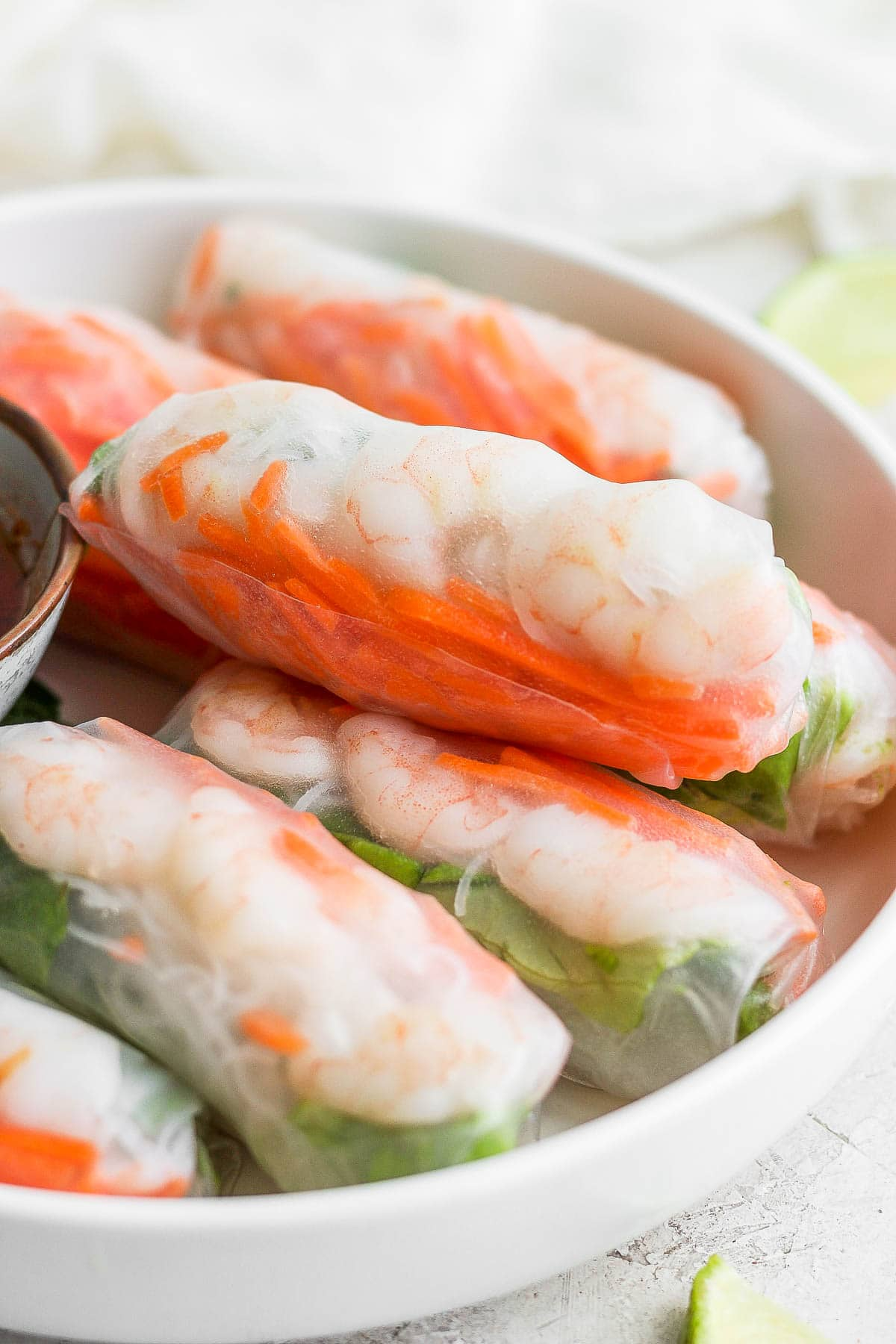 Side view of a bowl of shrimp spring rolls.