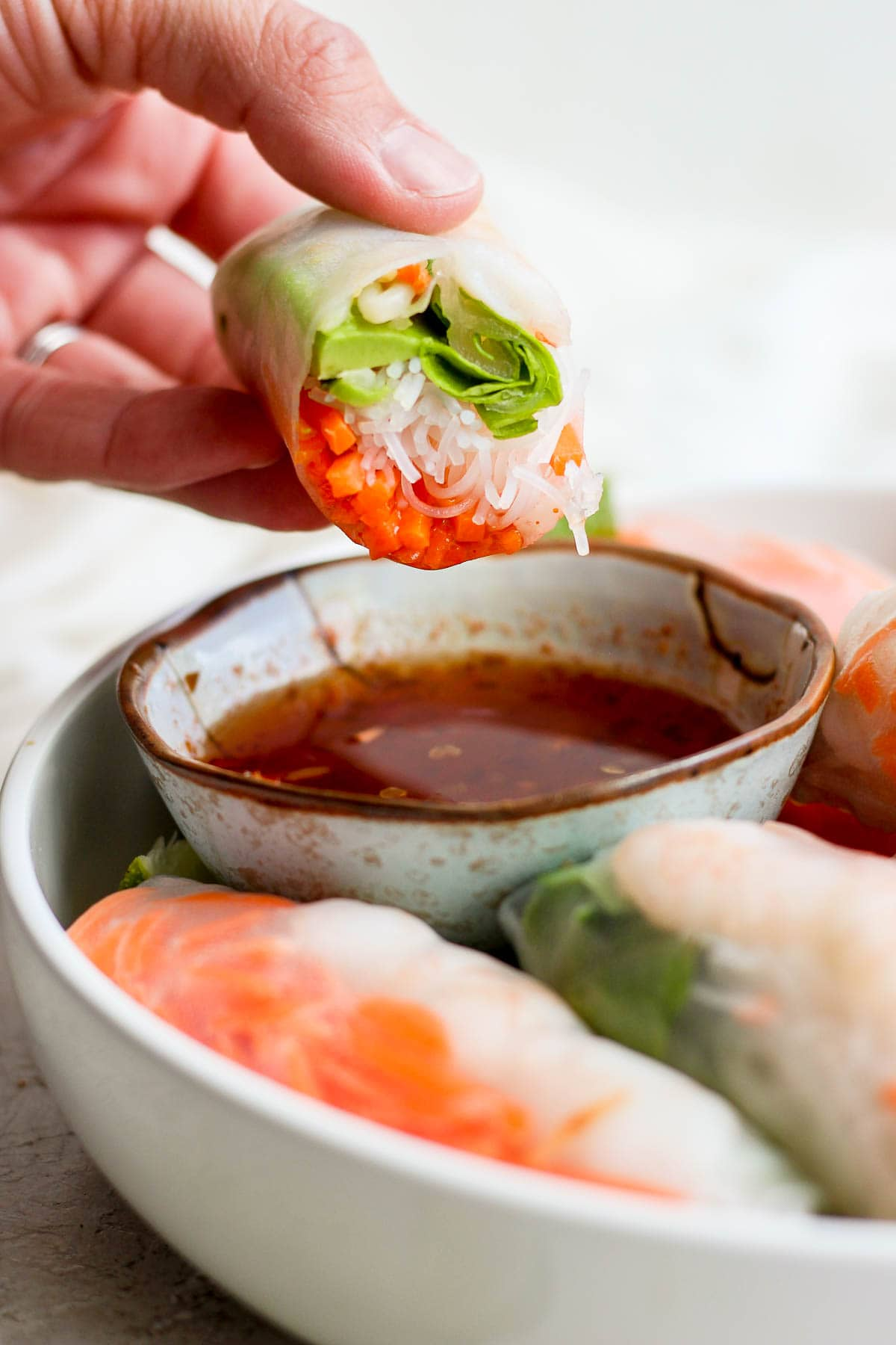 Someone dipping a shrimp spring roll into dipping sauce.
