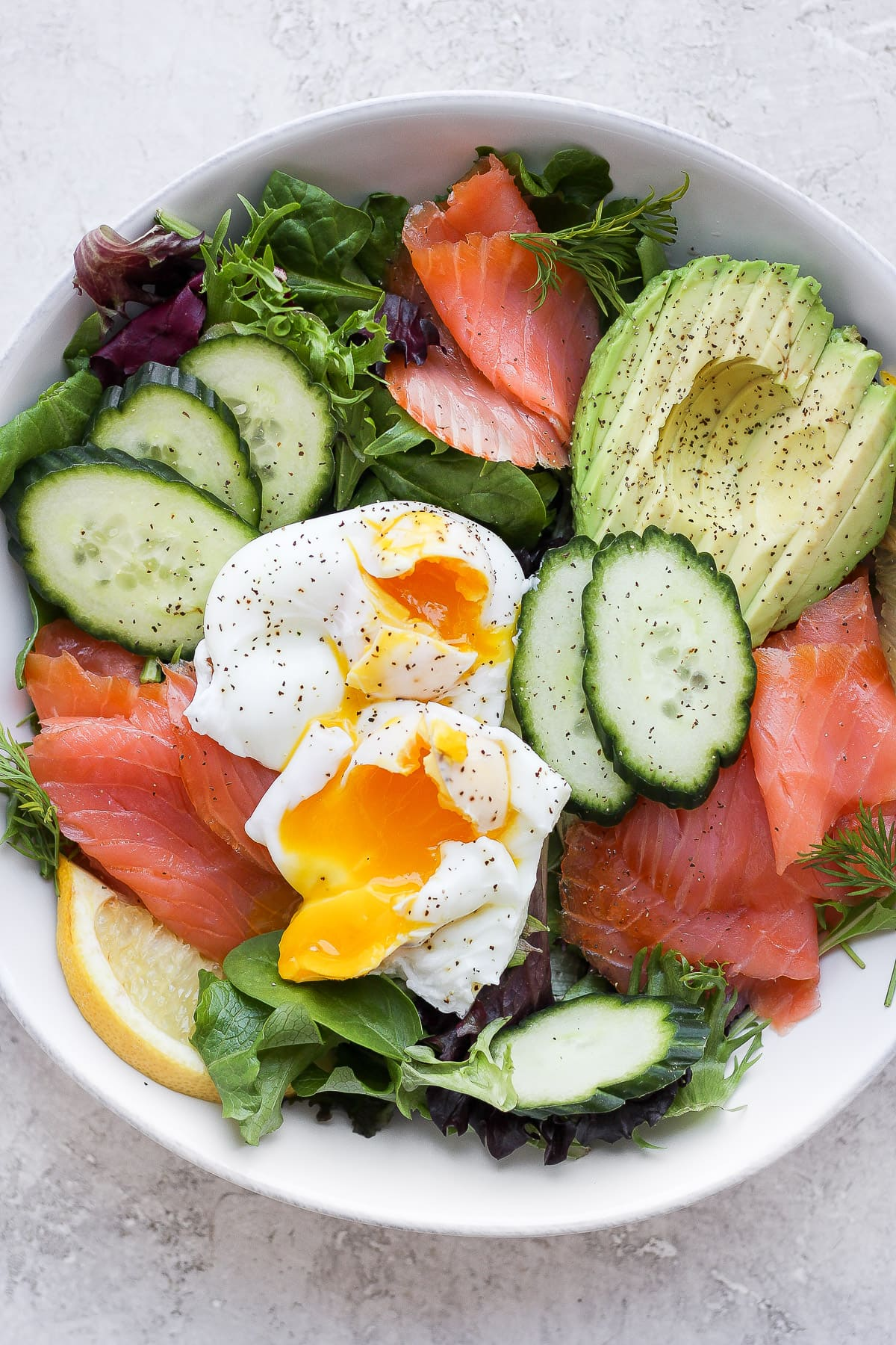Smoked salmon salad in a bowl with two poached eggs on top.