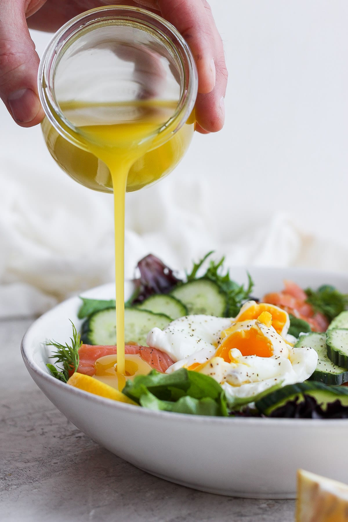 Someone pouring lemon dill vinaigrette into a bowl of salad.