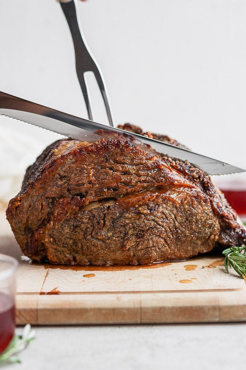 Prime rib on a cutting board with a knife cutting into it.