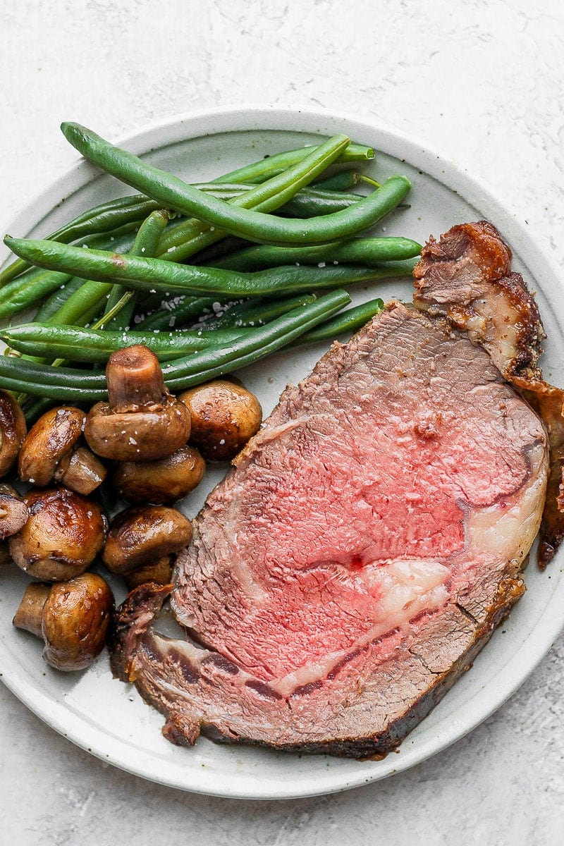 Plate of sautéed mushrooms, steamed green beans and a slice of prime rib.