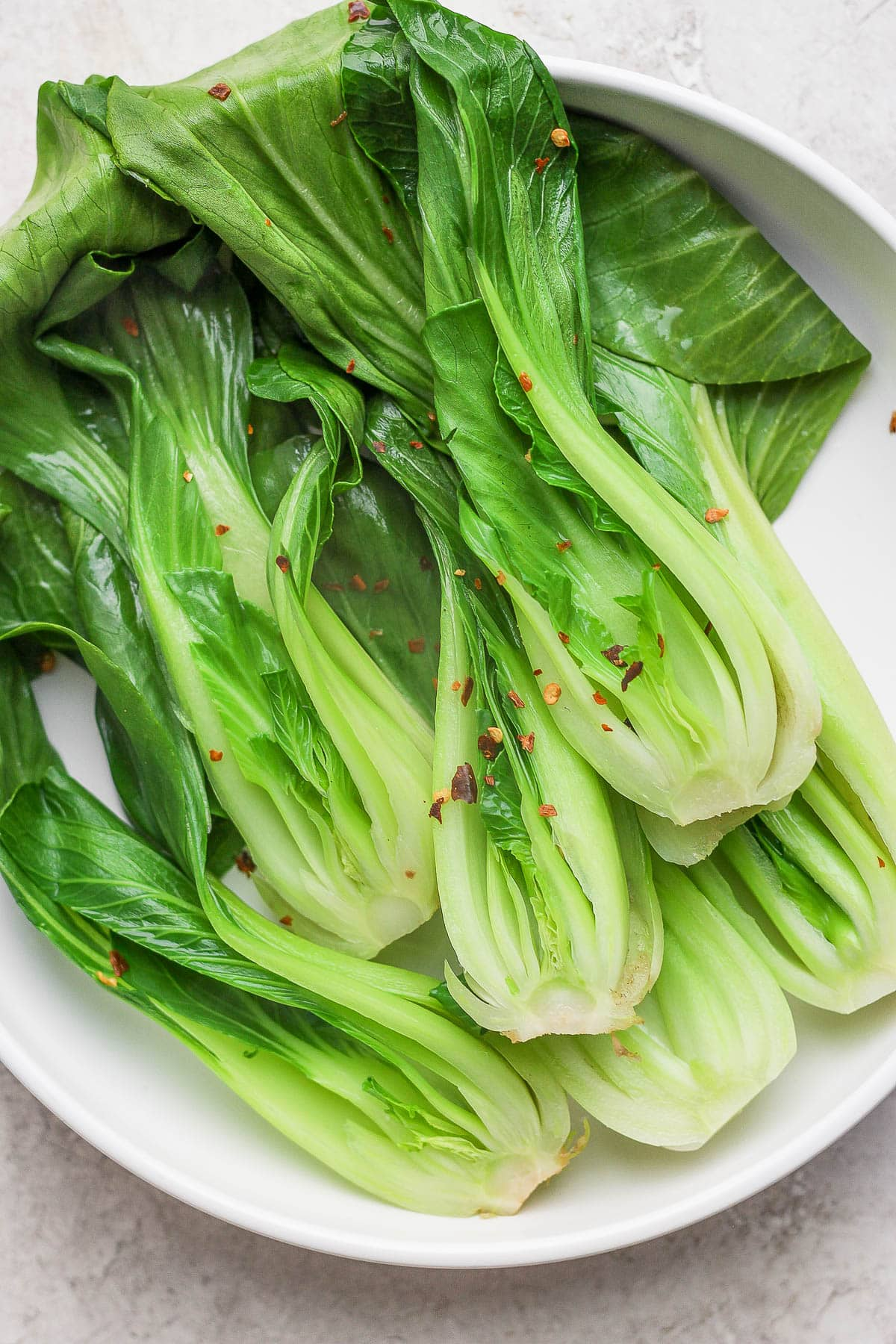 A large white bowl filled with braised bok choy and topped with red pepper flakes.
