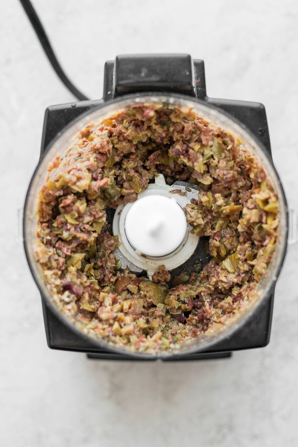 Top shot of a food processor with olive tapenade inside.