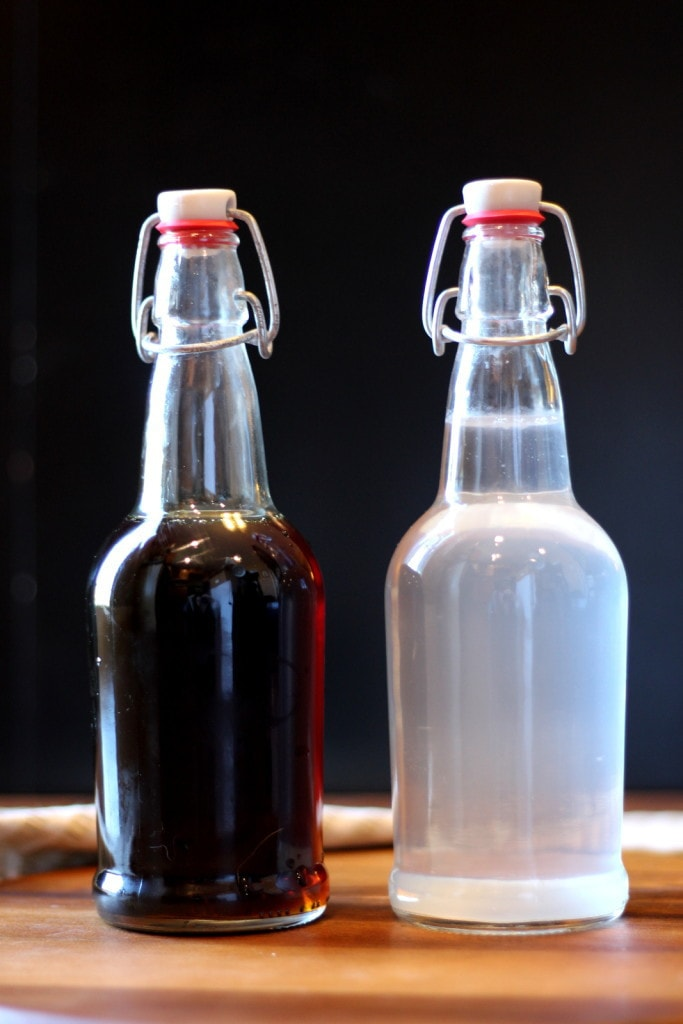 A bottle of maple syrup and a bottle of sap next to each other.