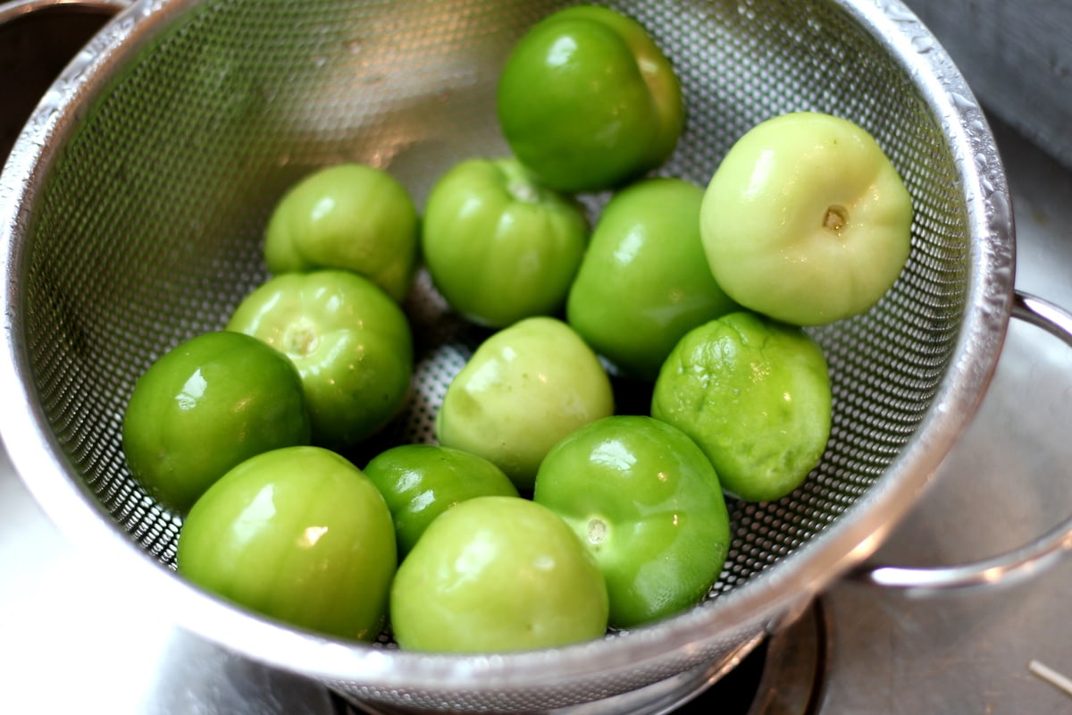 Tomatillos in a colander being rinsed.