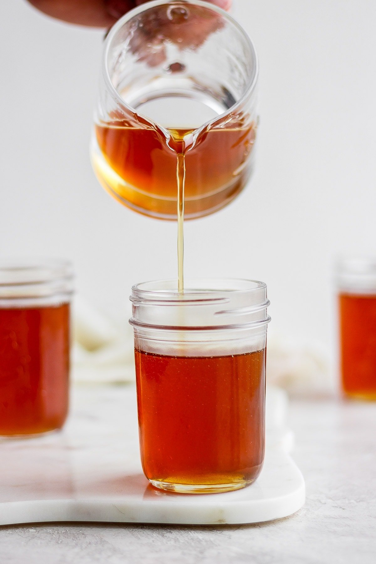 Someone pouring maple syrup into mason jars.
