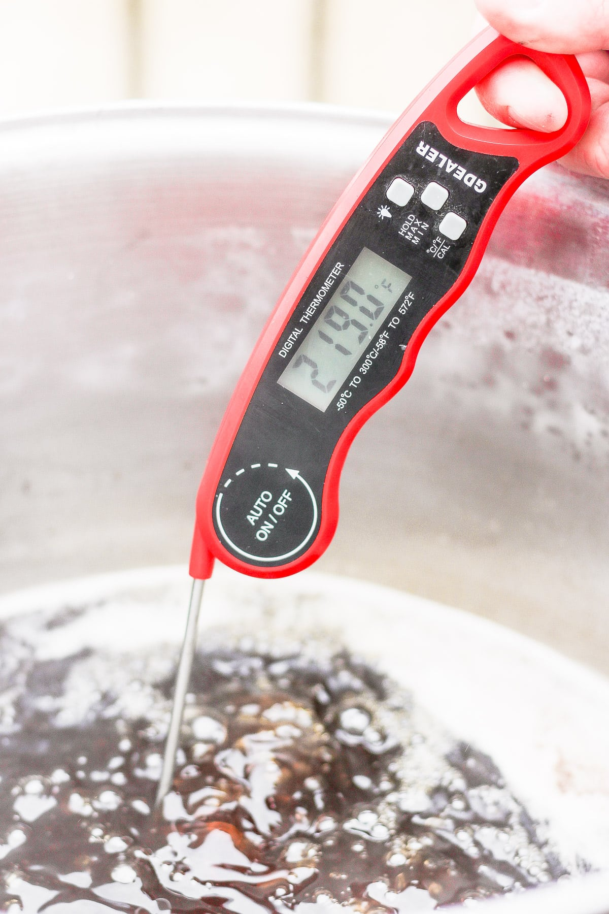 Maple syrup with a digital thermometer showing it is 219 degrees.
