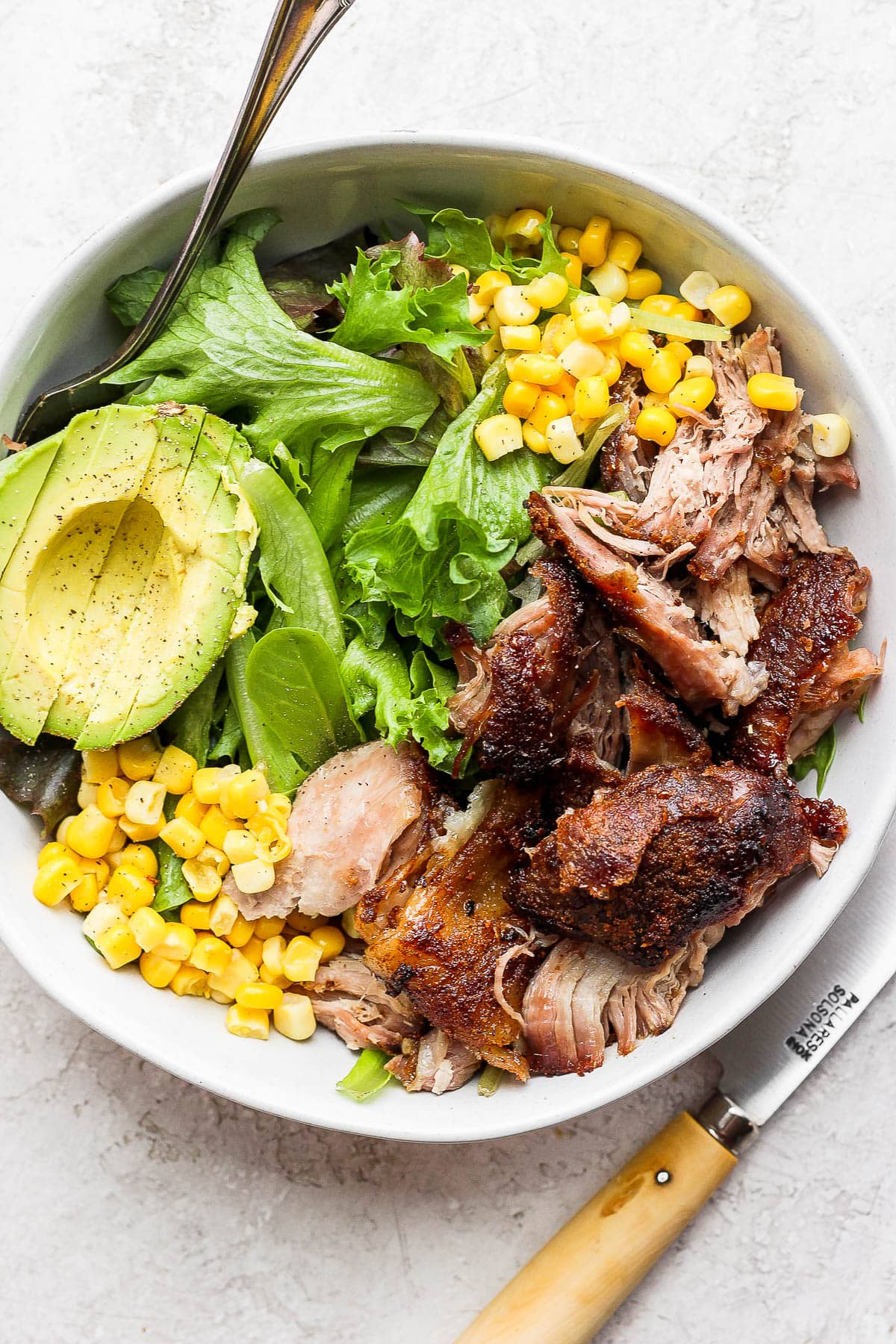 A pulled pork salad in a bowl with corn and avocado.