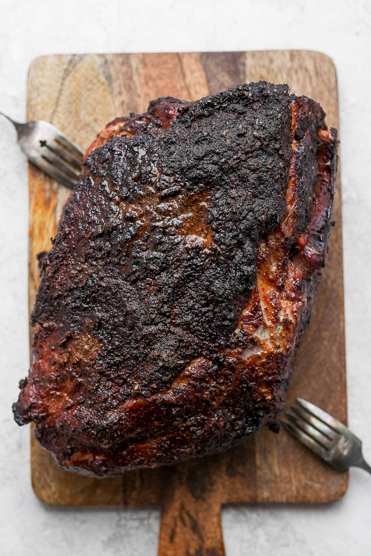 A smoked pork shoulder sitting on a wooden board.