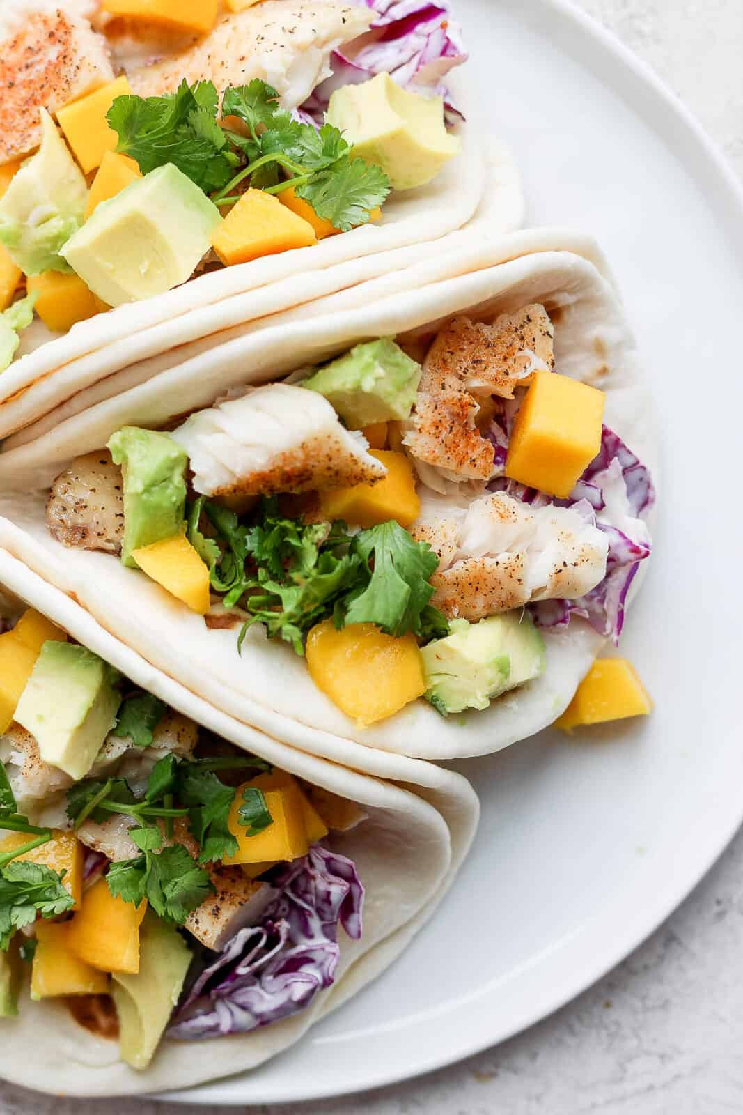 Three tilapia fish tacos with mango and avocado on a white plate.
