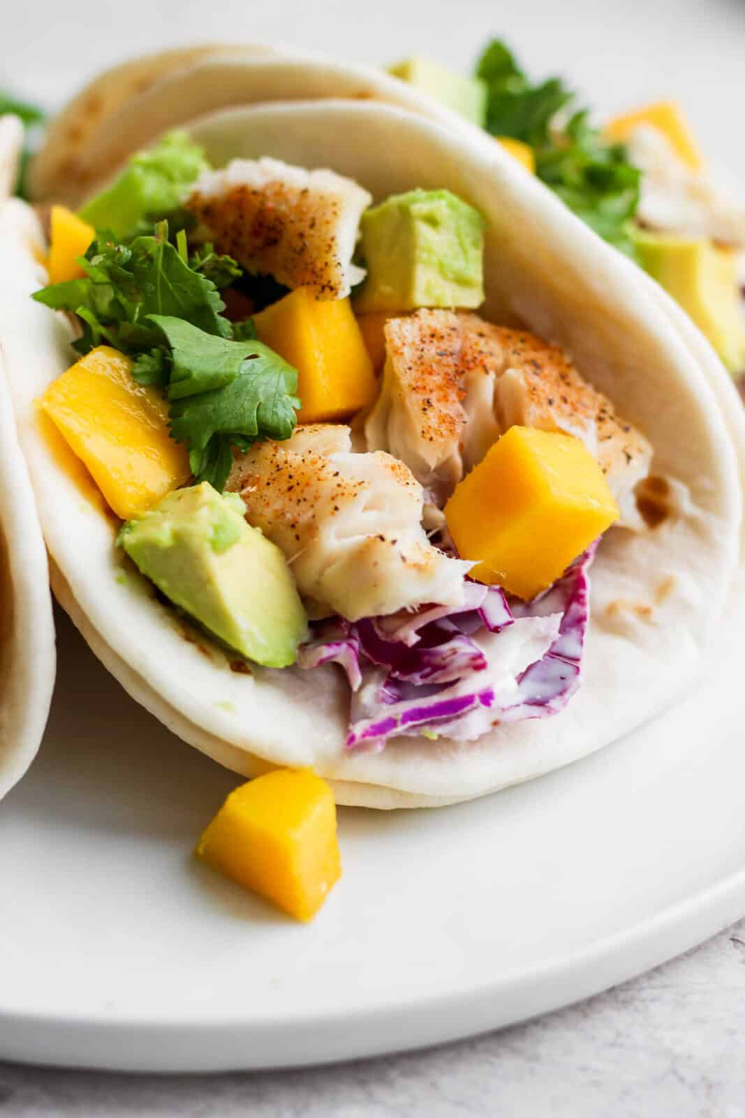 A tilapia fish taco with mango and avocado on a white plate.
