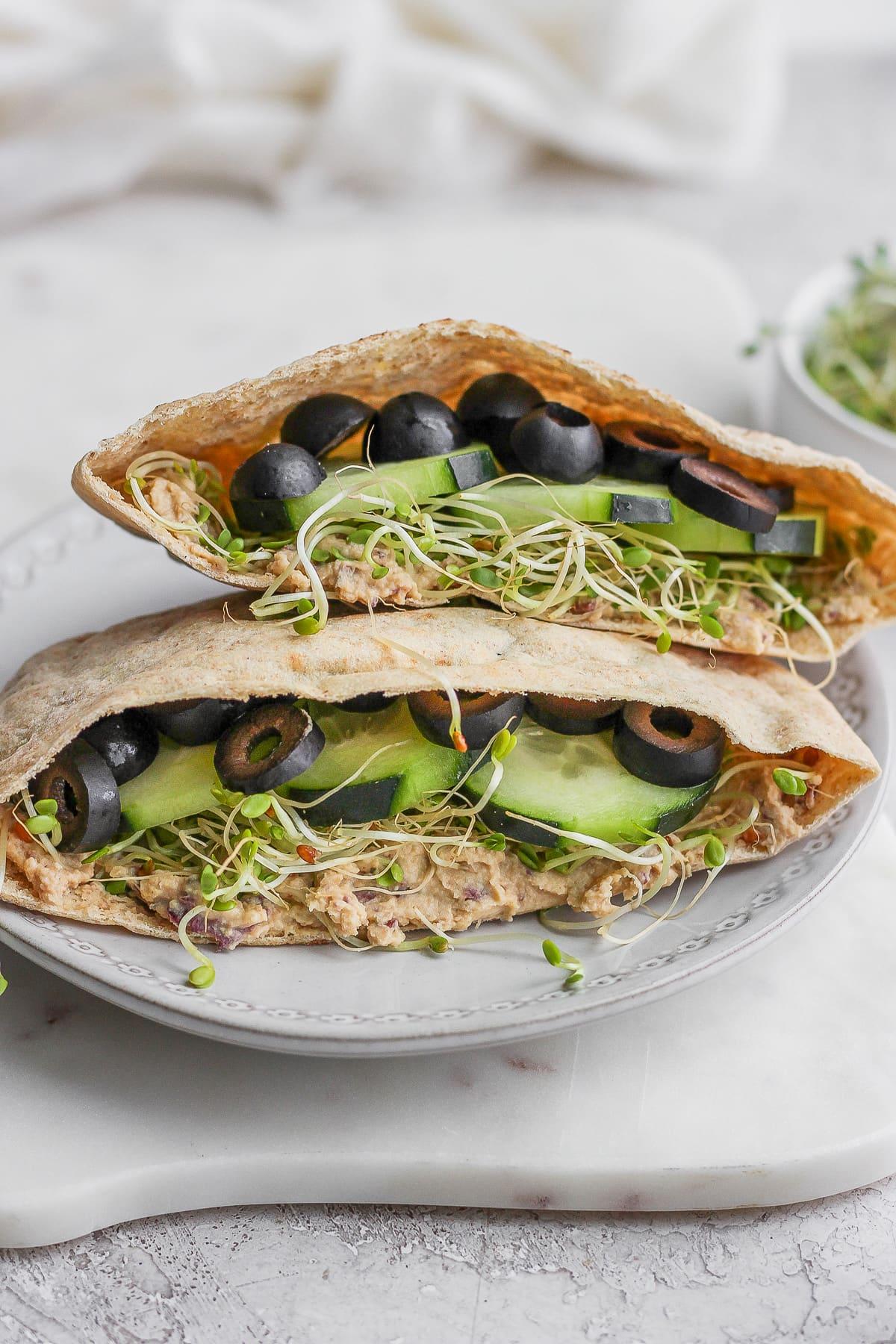 A vegan pita sandwich sitting on a plate.