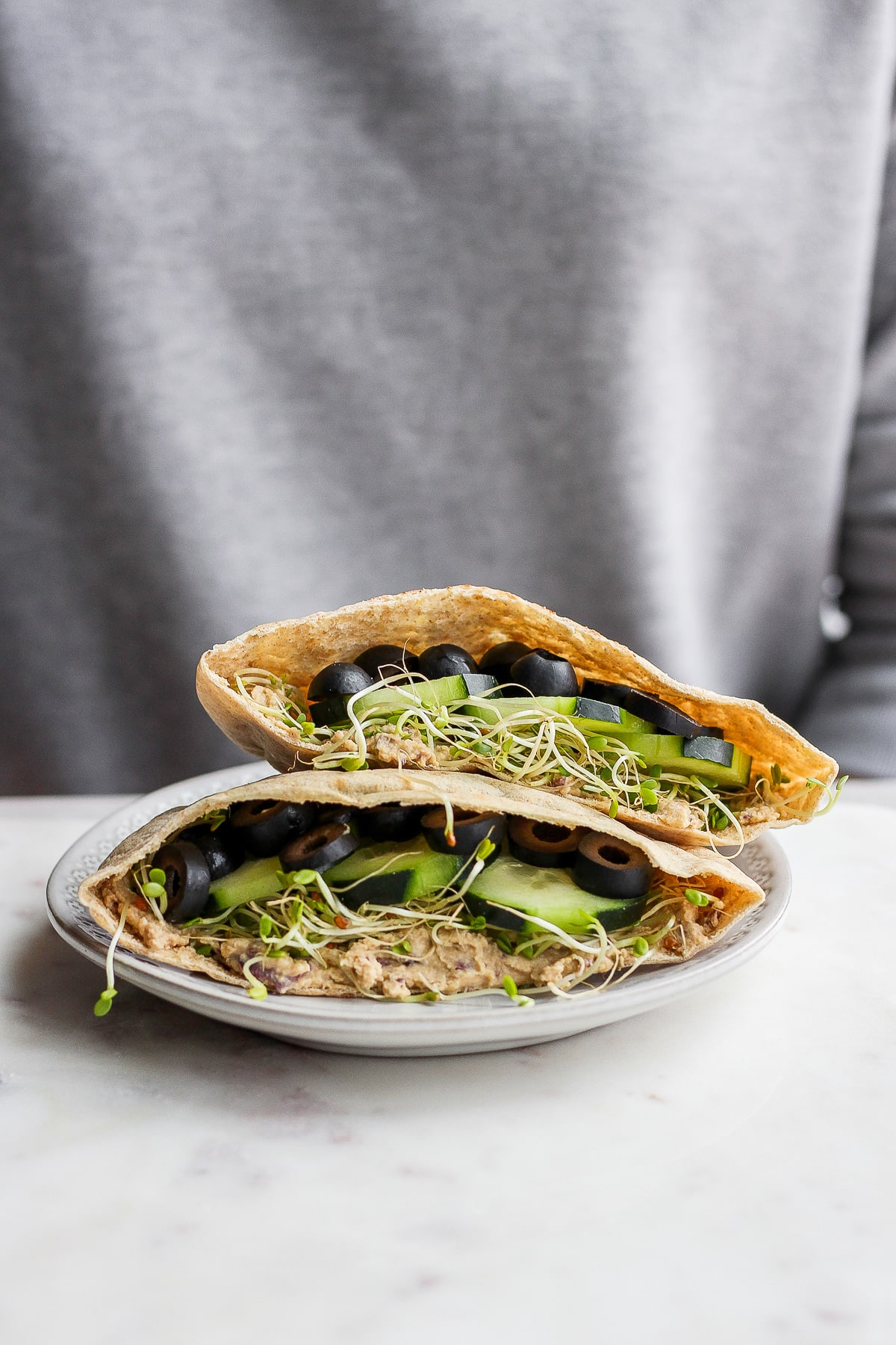 A vegan pita sandwich sitting on a plate in from of someone.