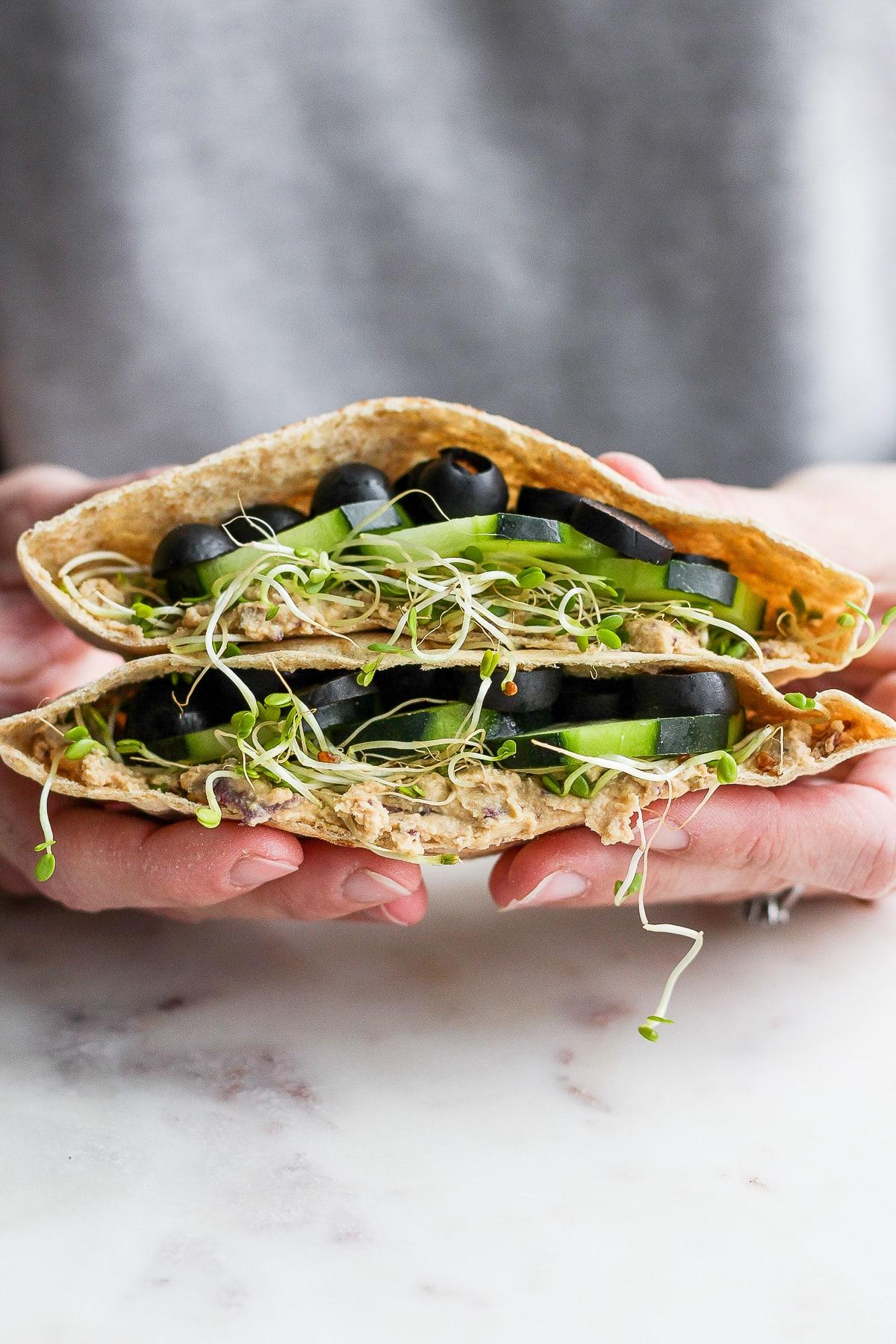 Someone holding two sides of a vegan pita sandwich.