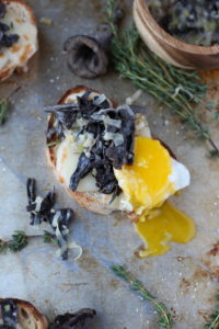 Creamy Leek and Wild Black Trumpet Mushrooms on Cheesy Toast with Egg Over Easy. An awesome small plate, appetizer or breakfast recipe. thewoodenskillet.com #foodphotography #foodstyling