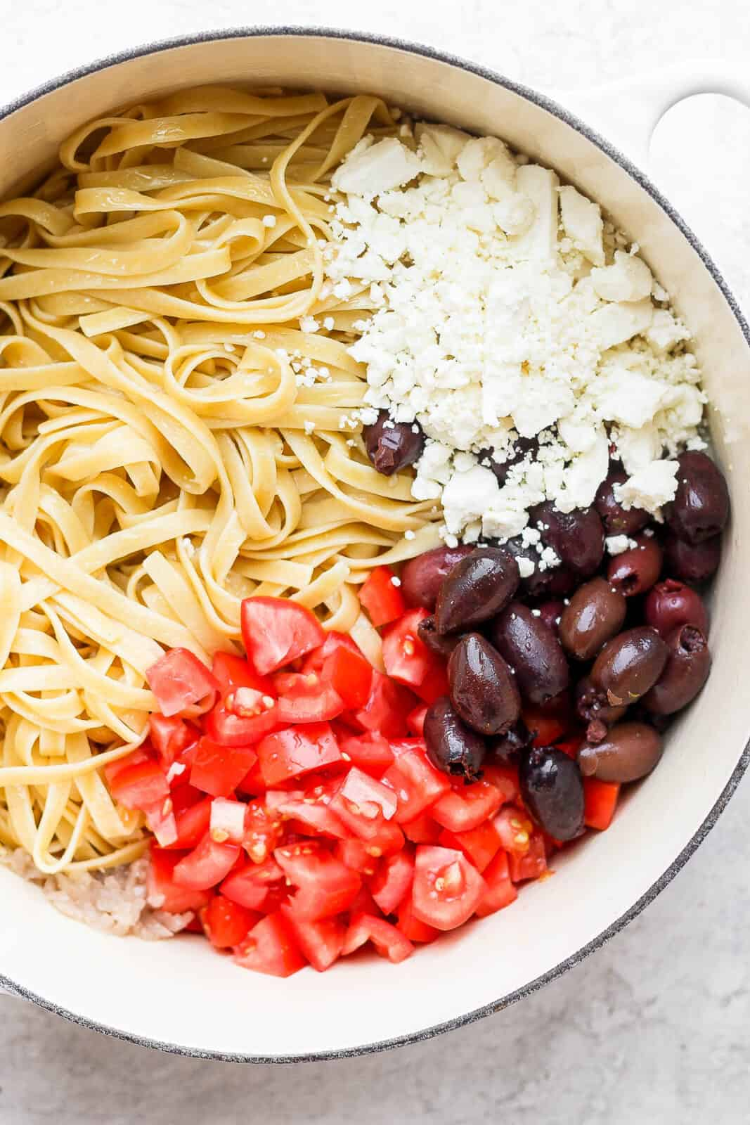 Pan of cooked noodles with feta, olives and tomato.