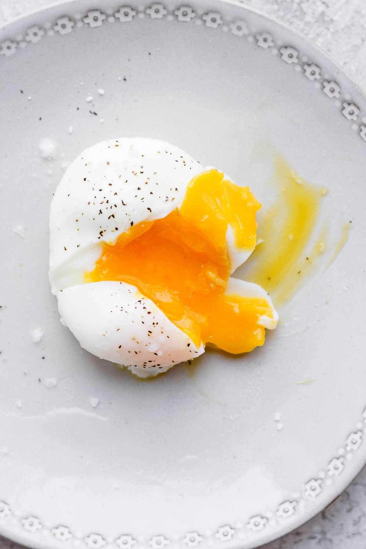 A poached egg on a plate, cut open with the yolk coming out.