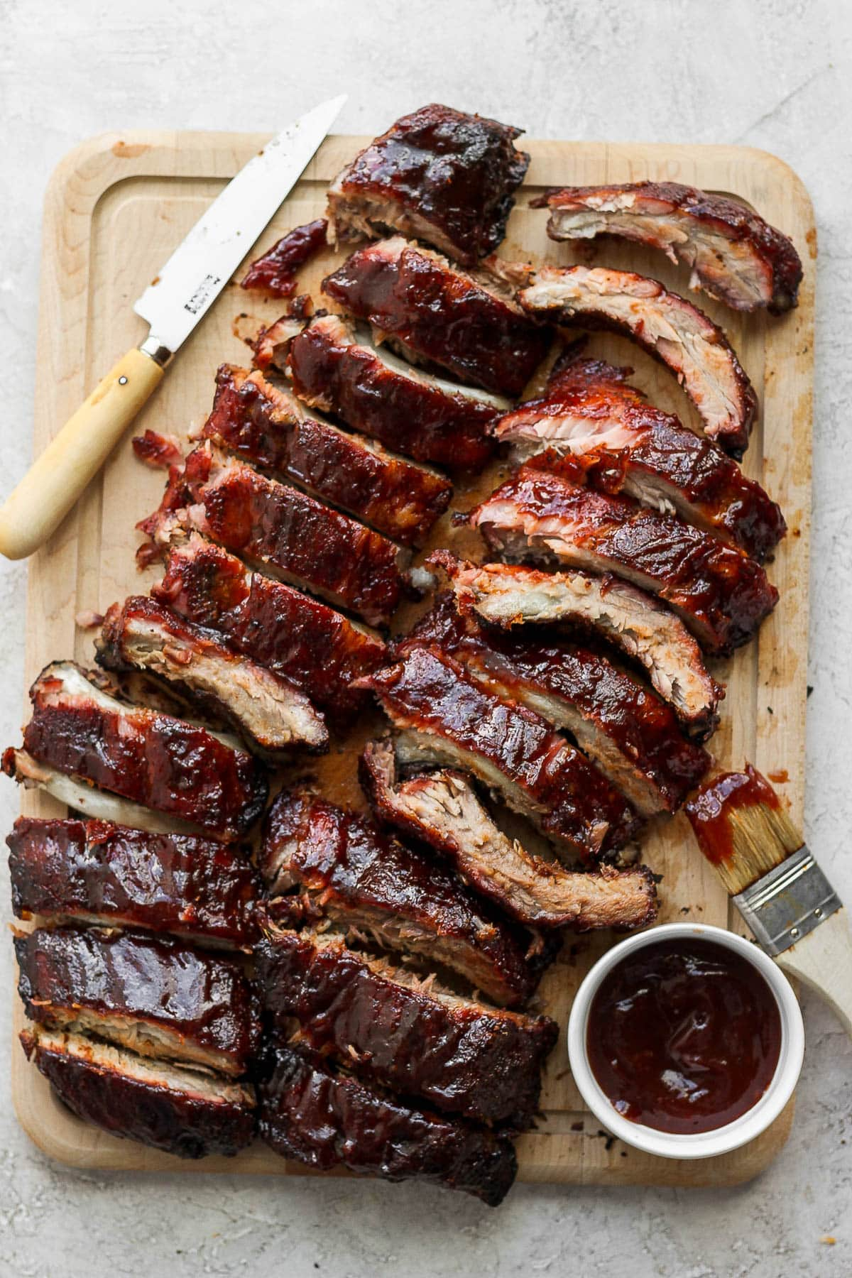 A wooden cutting board with two racks of smoked ribs sitting on top.