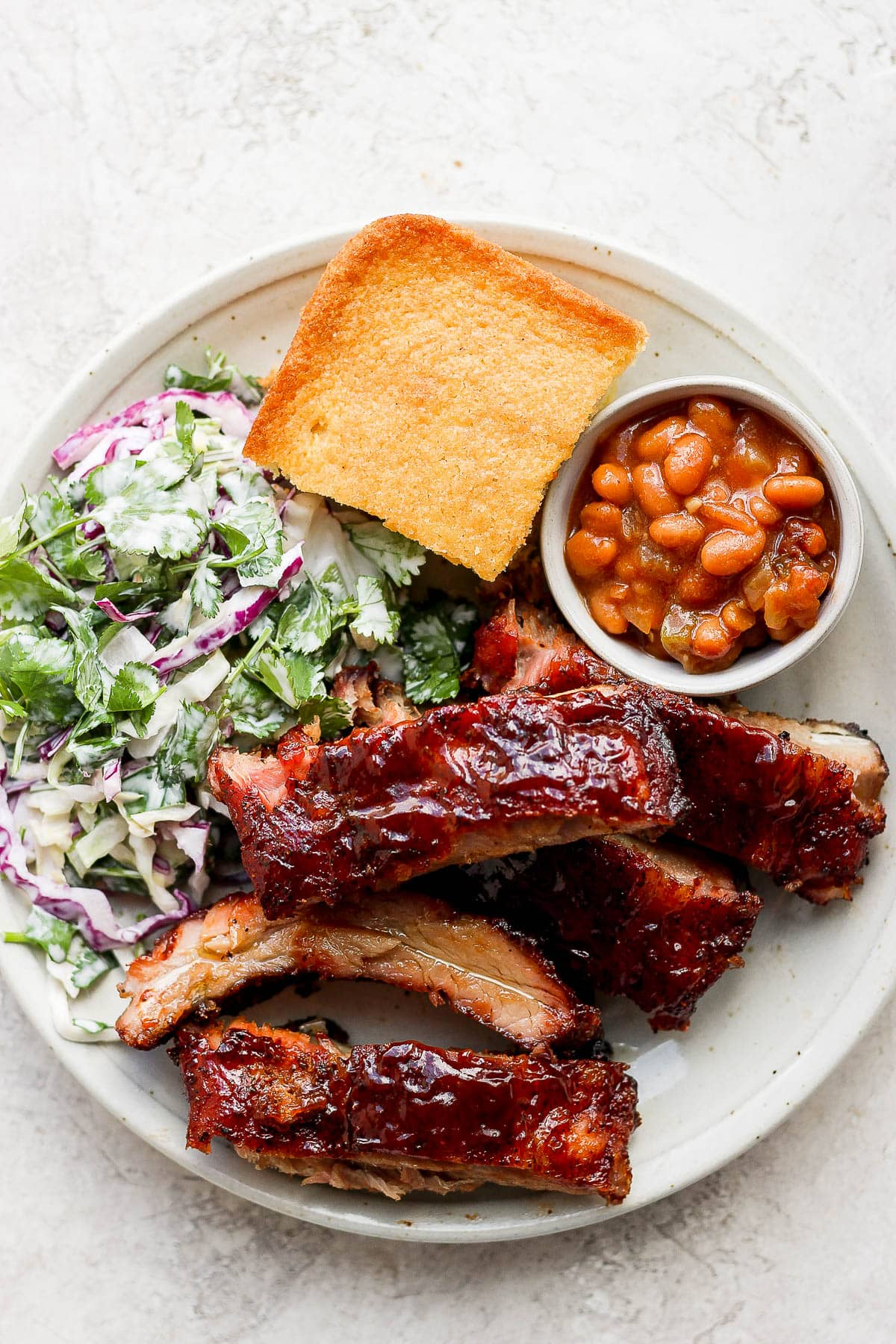 A plate filled with smoked baby back ribs, smoked beans, coleslaw and cornbread.