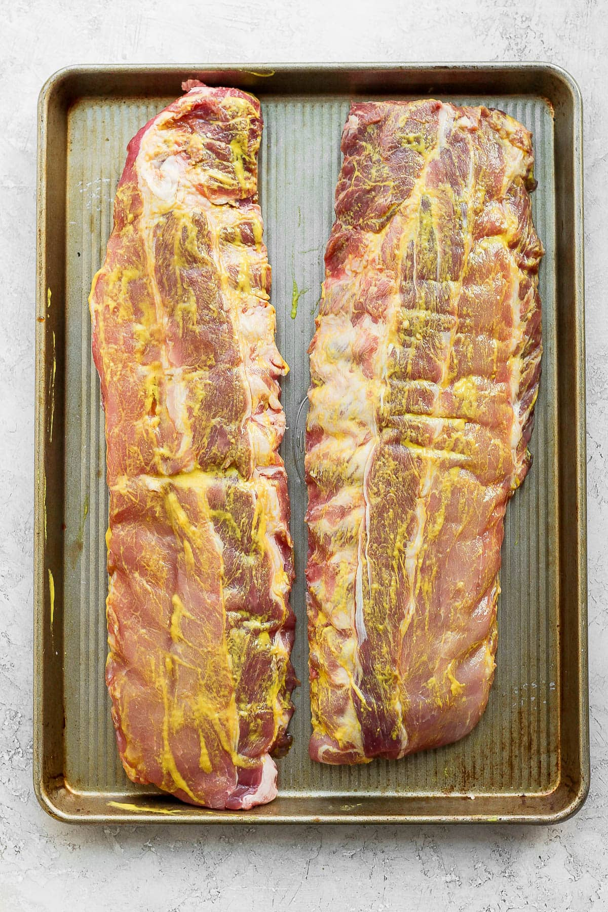 Two racks of ribs sitting on a metal baking sheet and yellow mustard rubbed all over them.