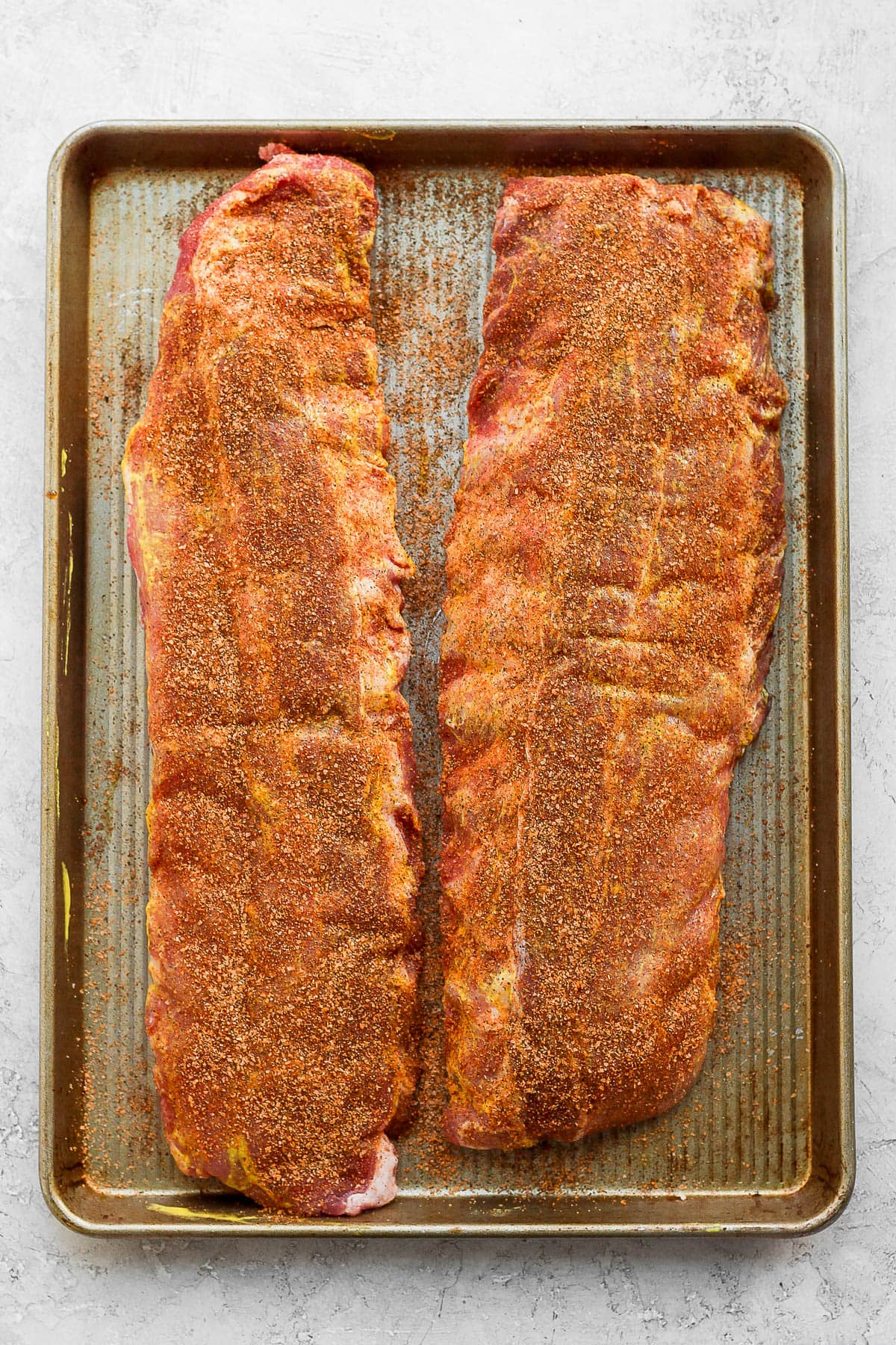 Two racks of ribs sitting on a metal baking sheet and dry rub rubbed all over them.