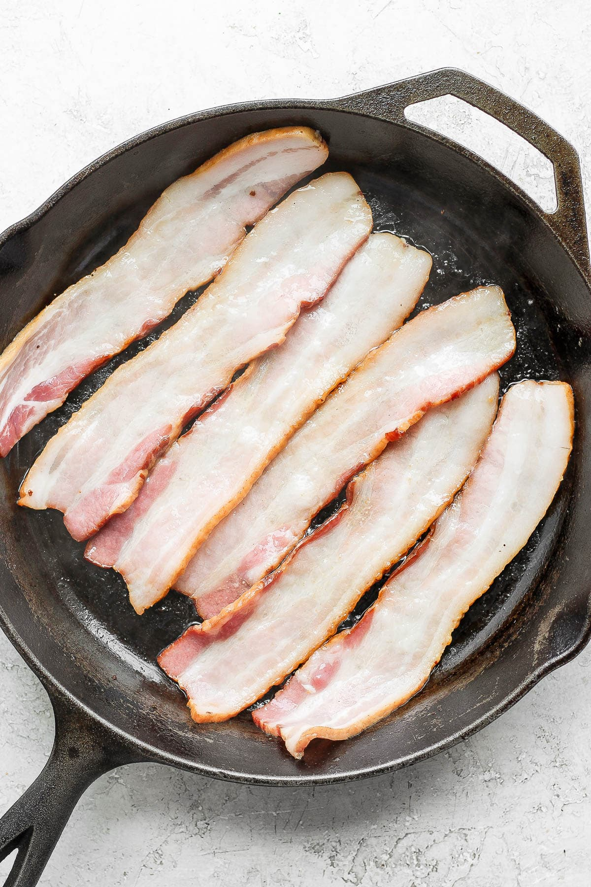 Six pieces of bacon cooking in a cast iron skillet.