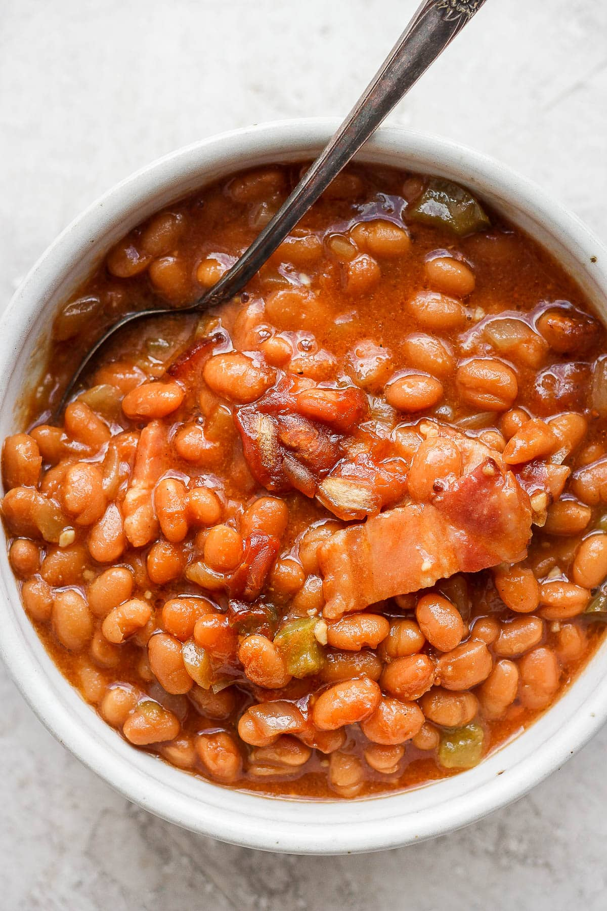 Bowl of smoked baked beans with a spoon sticking out.