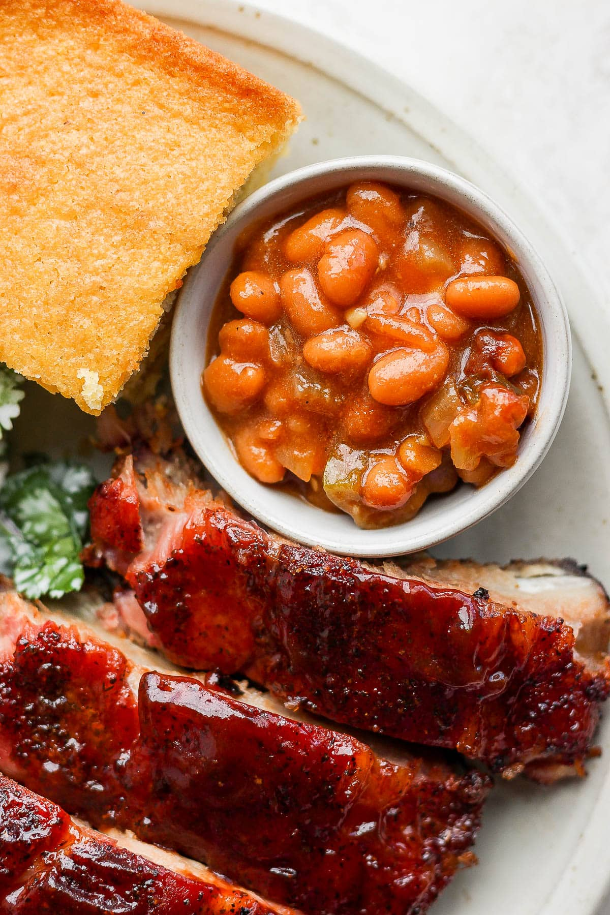 Smoked Baked Beans in a small bowl sitting on top of plate next to smoked rib and cornbread.
