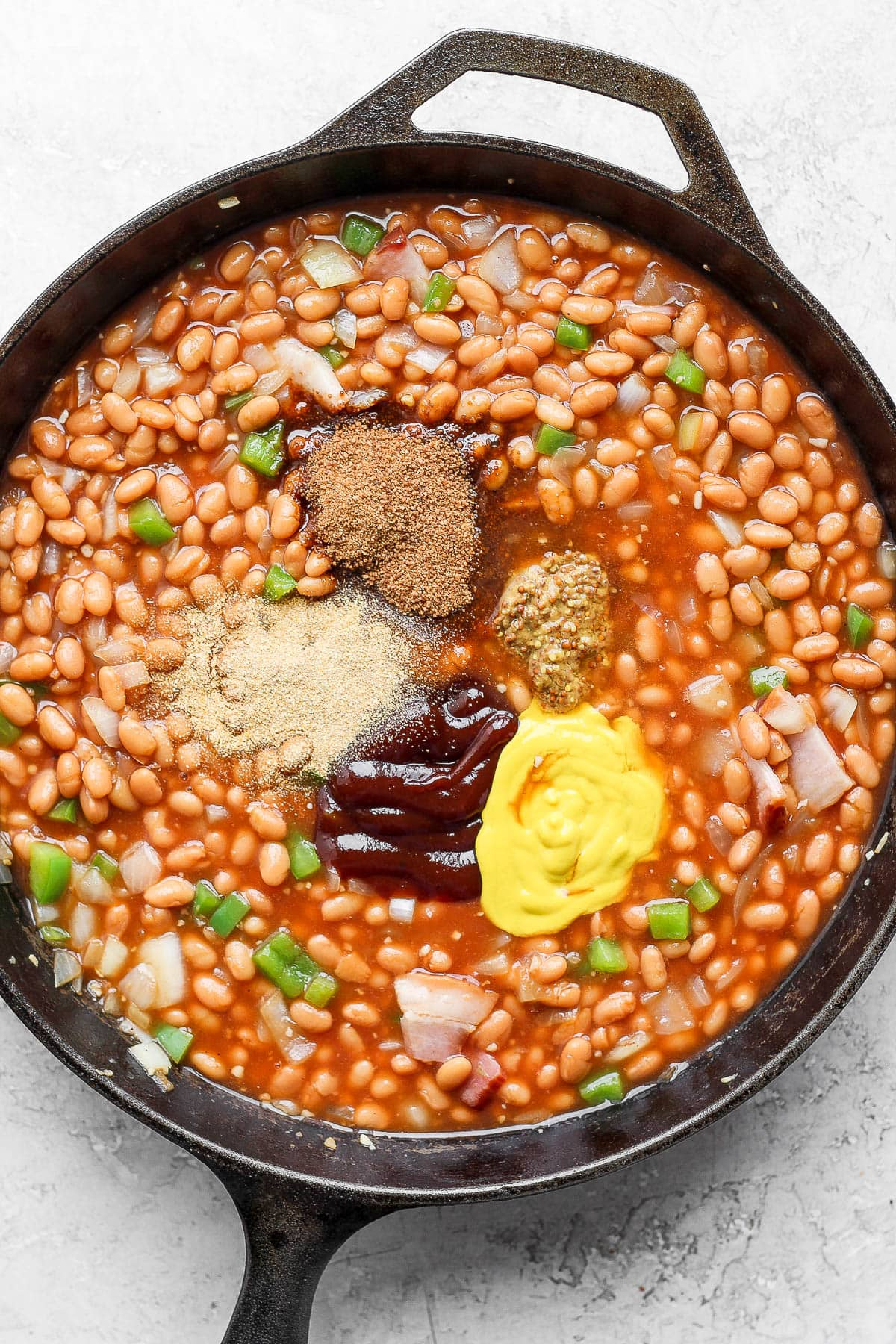All the ingredients in a cast iron pan to make baked beans.