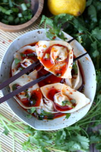 Spicy Pork Wontons + Red Chili Broth. Succulent wontons filled with pork, fennel and shallots sitting in a unique and flavorful chicken broth and drizzled in red chili oil. Comfort food at its finest! thewoodenskillet.com #foodphotography #foodstyling