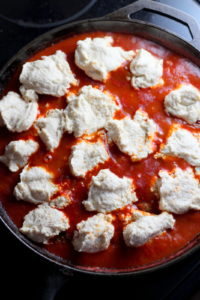 Meatballs and Dumplings - recipe for pillow soft dumplings served with meatballs simmered in tomato sauce. Perfect recipe for a weeknight meal! thewoodenskillet.com