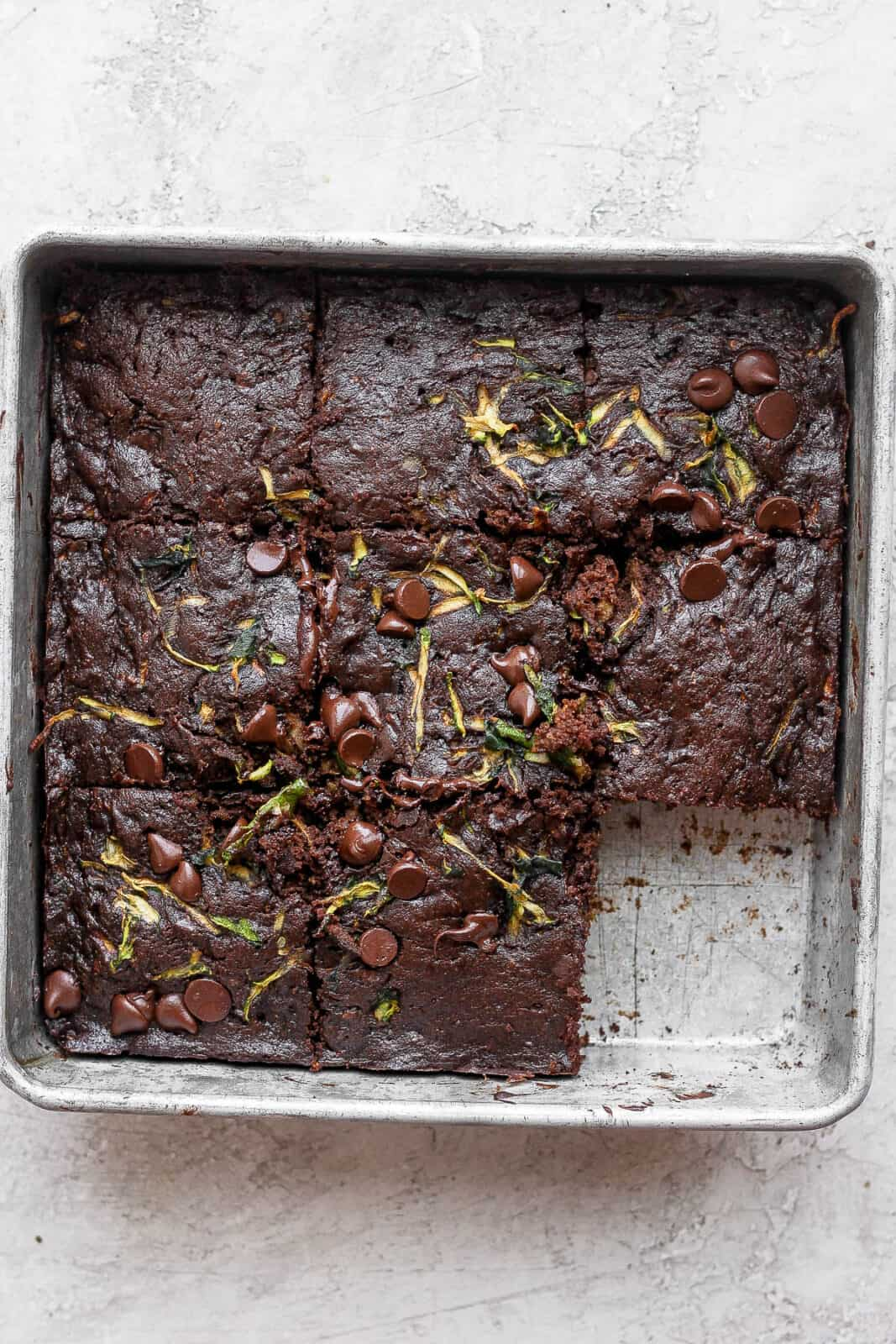 Zucchini brownies in a pan cut into squares and one missing.