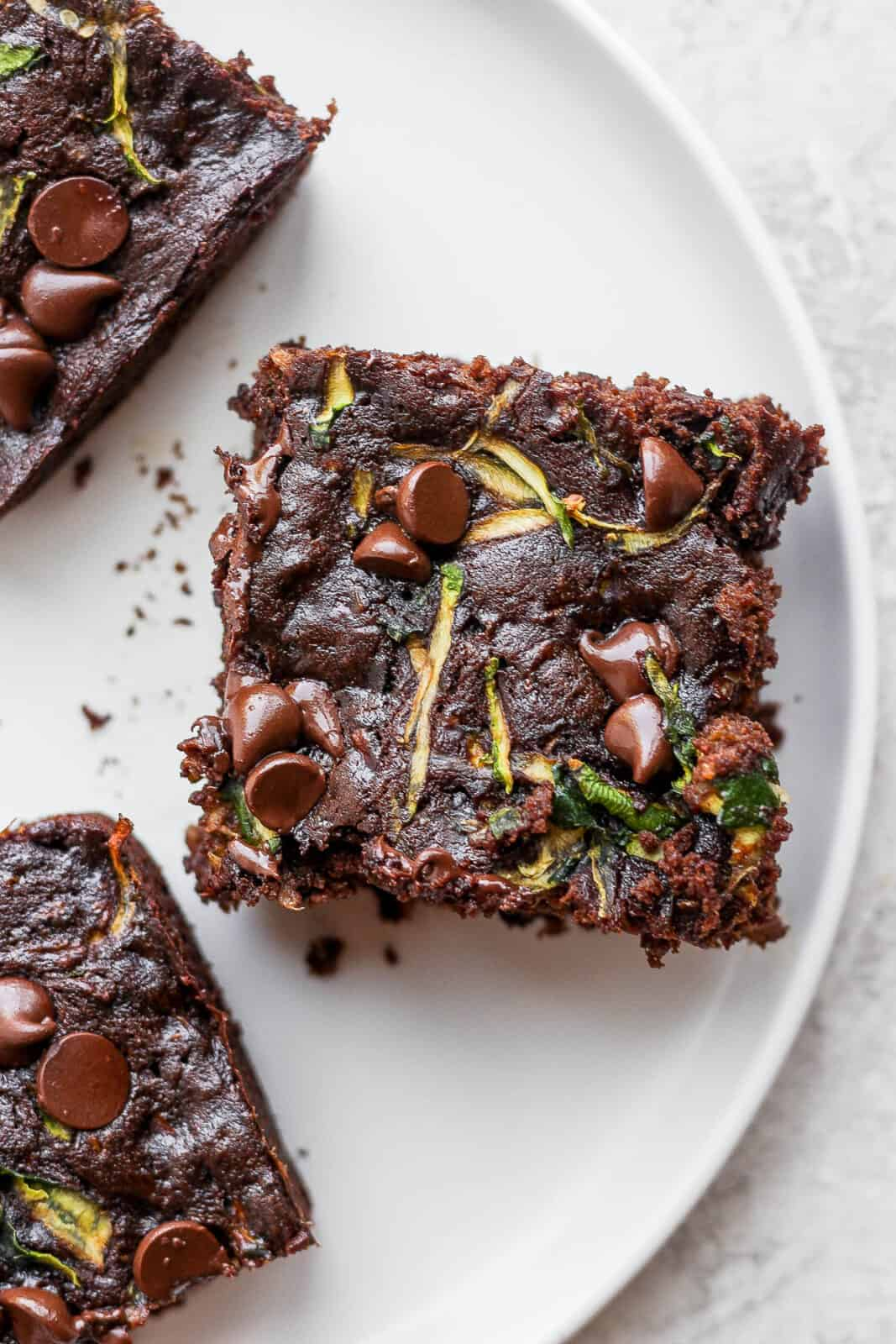 Three zucchini brownies on a plate.