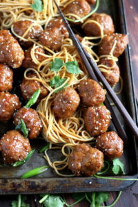 Sesame Soy Ginger Meatballs + Noodles. Easy to make meatball recipe, baked in a soy ginger sauce served over chow mien noodles. thewoodenskillet.com