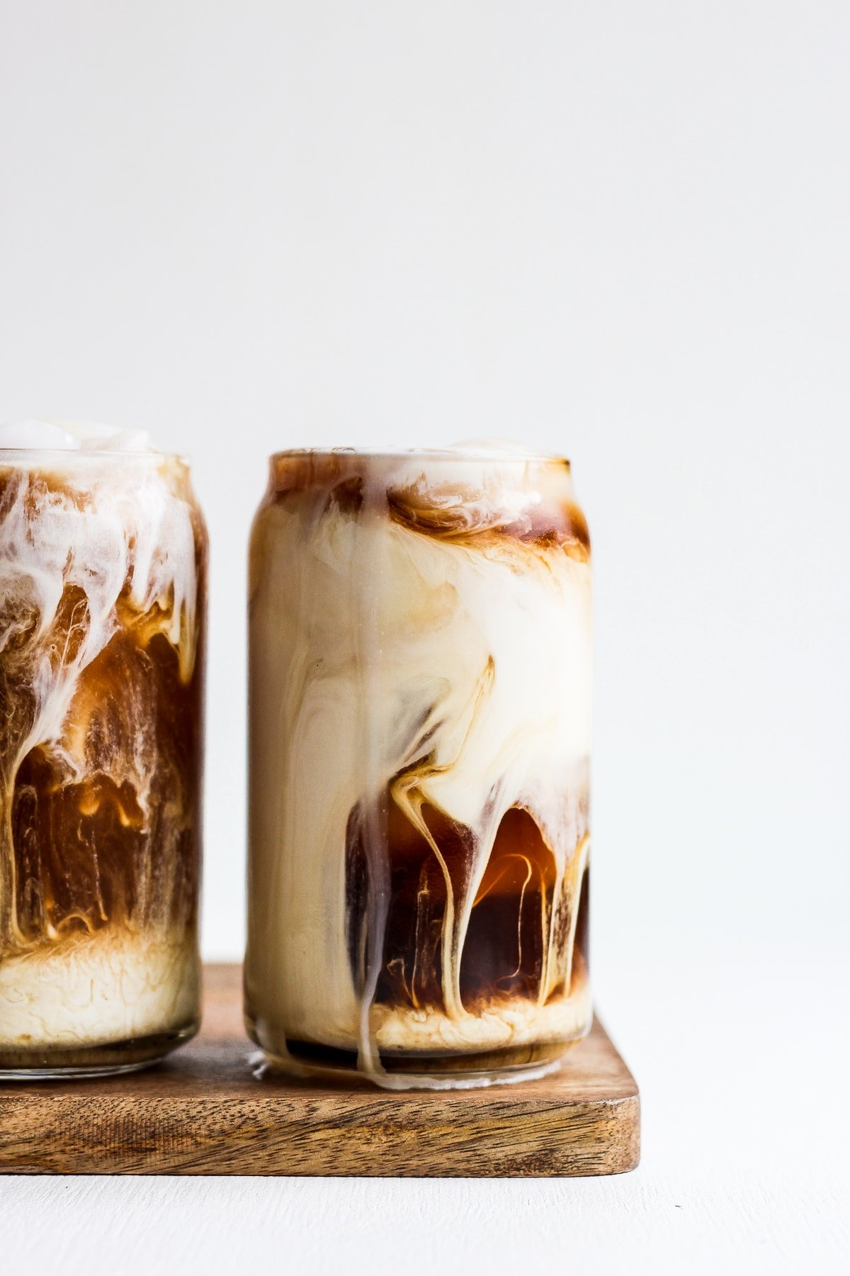 A glass of cold brew coffee with creamer swirling inside.