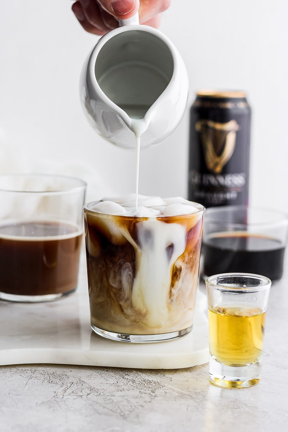 A glass of Irish Cold Brew Coffee with creamer being poured into it.