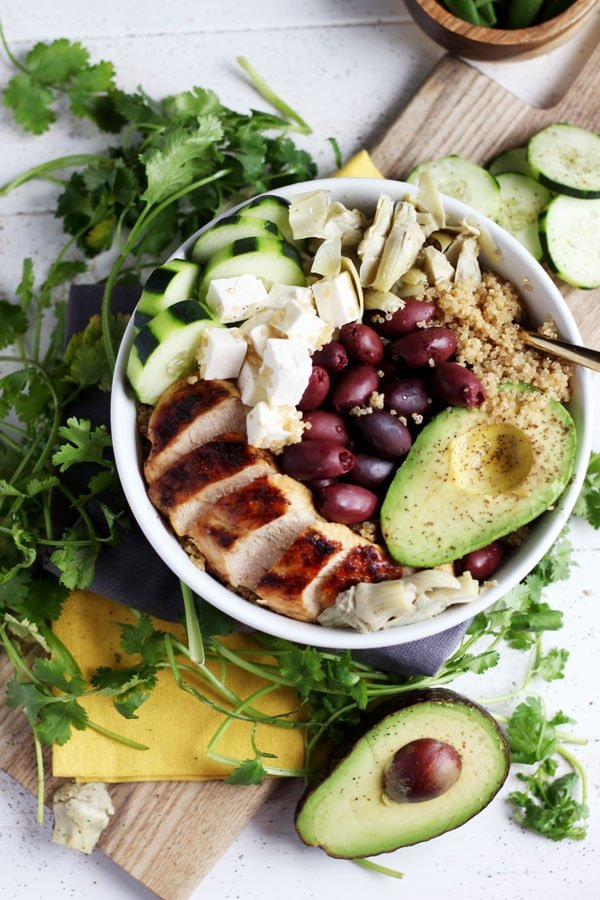 Bowl of quinoa, chicken, feta cheese, olives, cucumber and avocado.