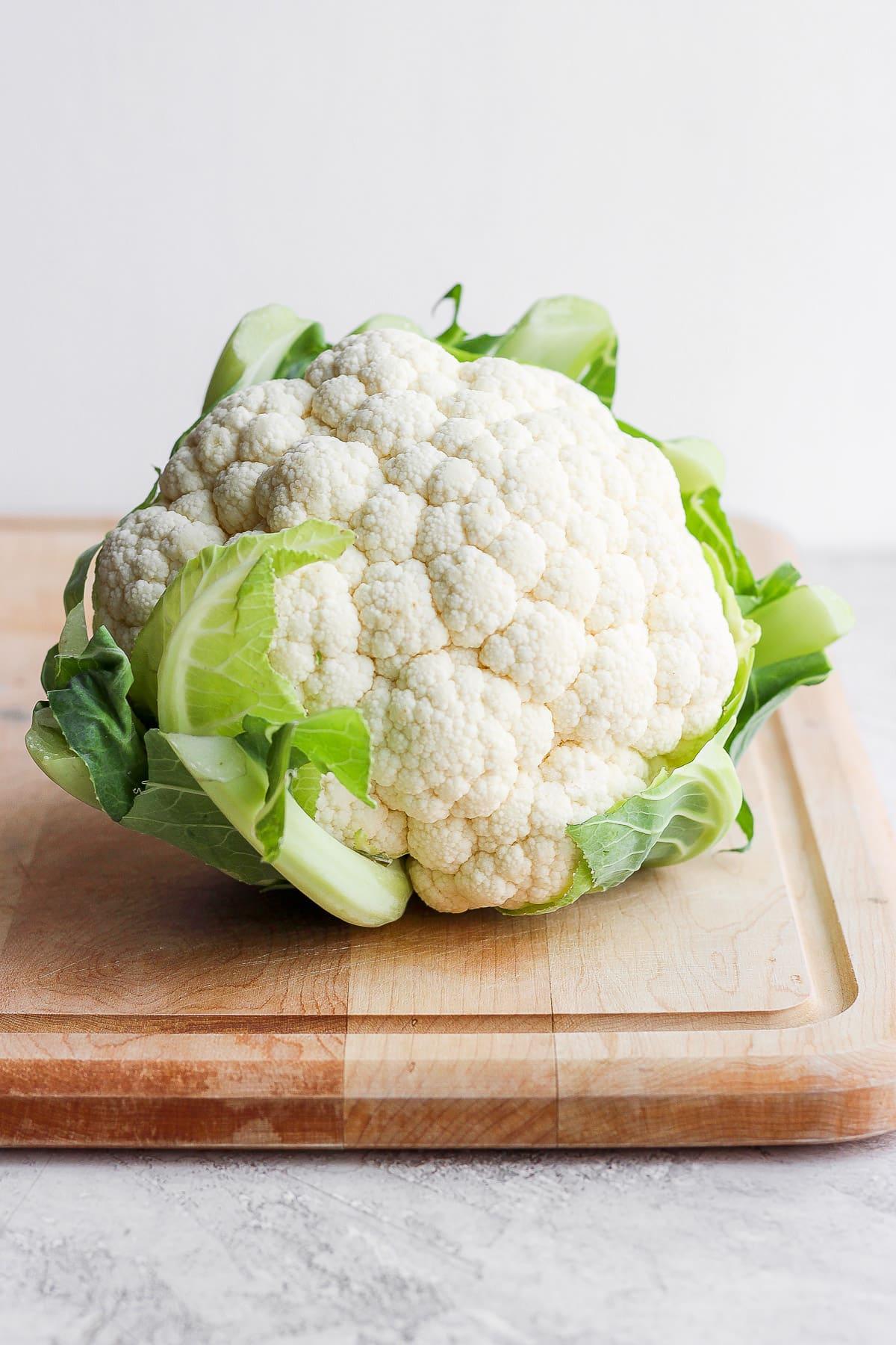 A head of cauliflower sitting on a cutting board.