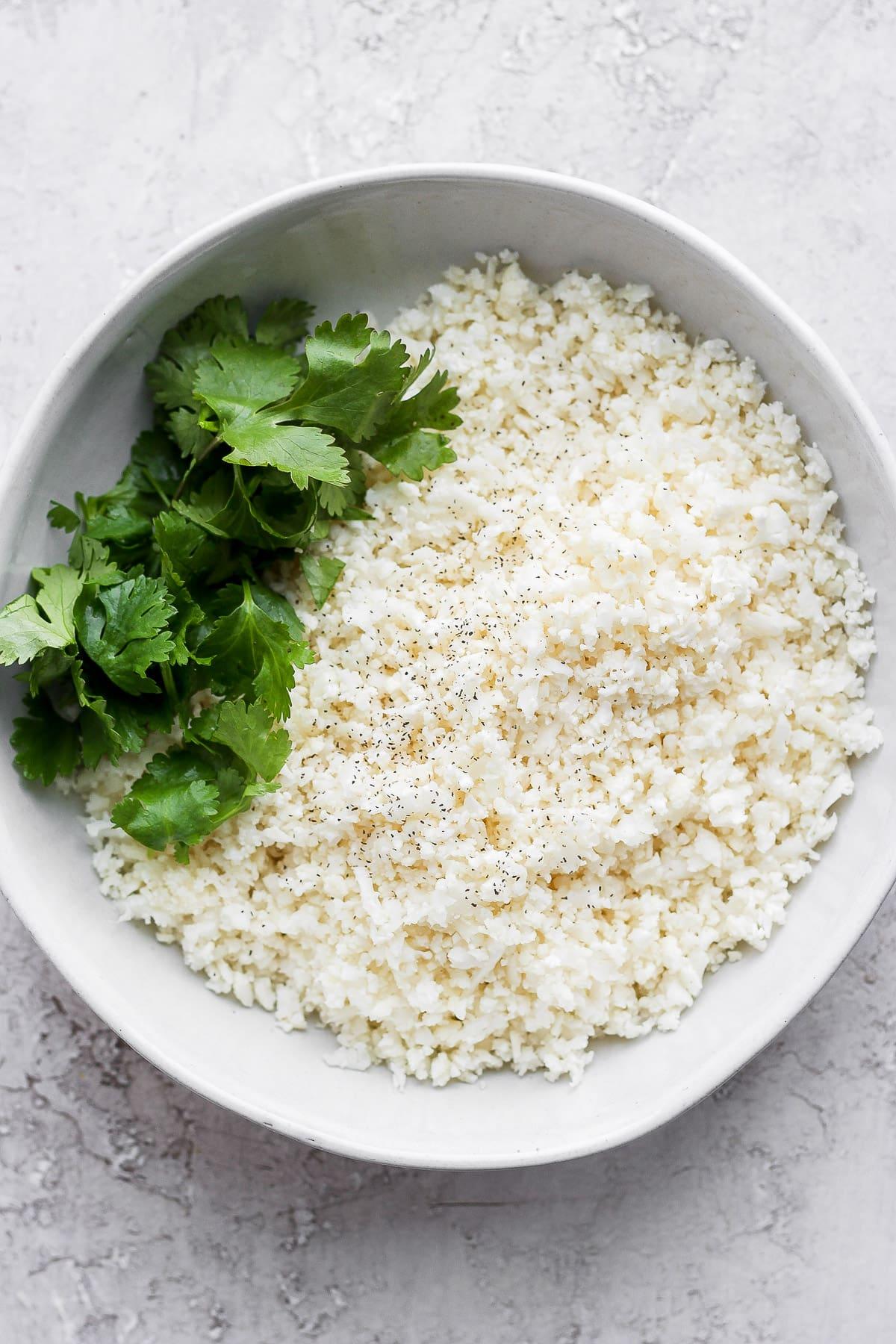 Cauliflower in a bowl with fresh cilantro.