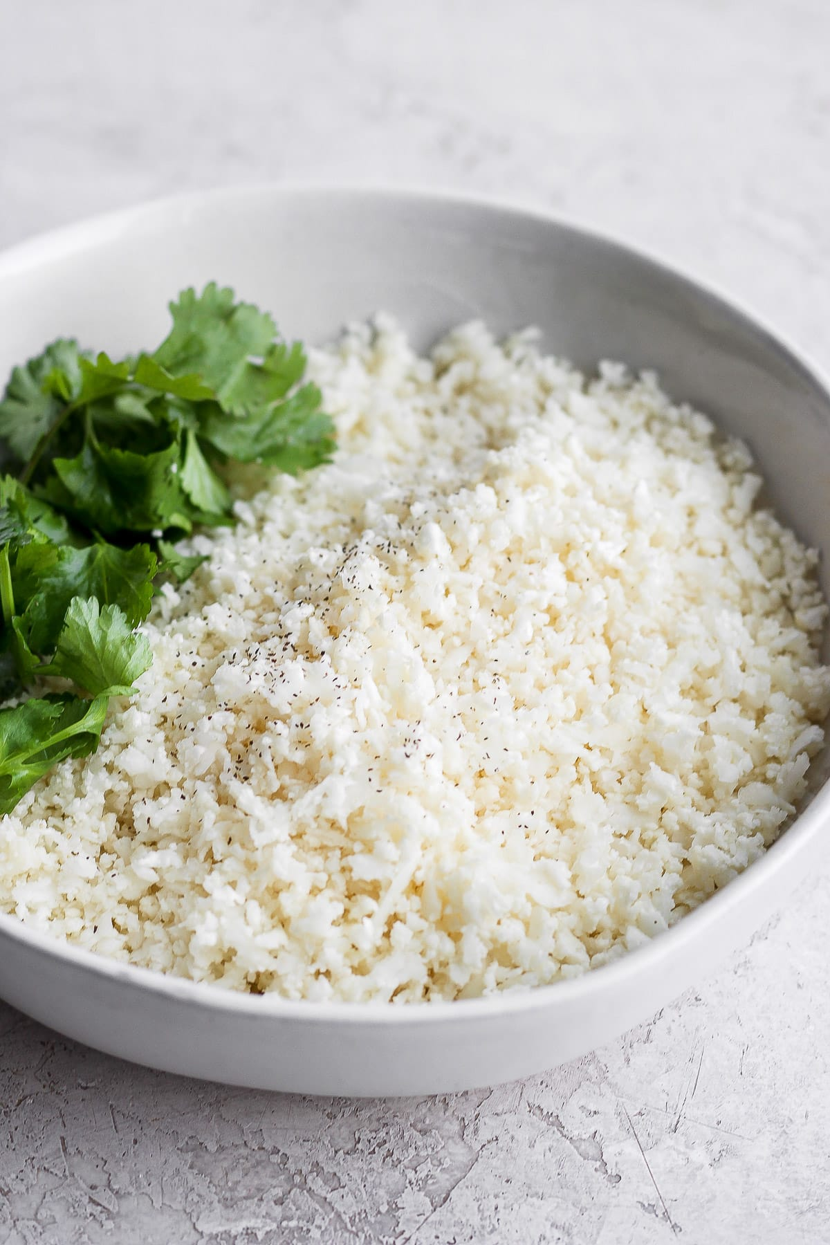 Cauliflower rice in a bowl with fresh cilantro.