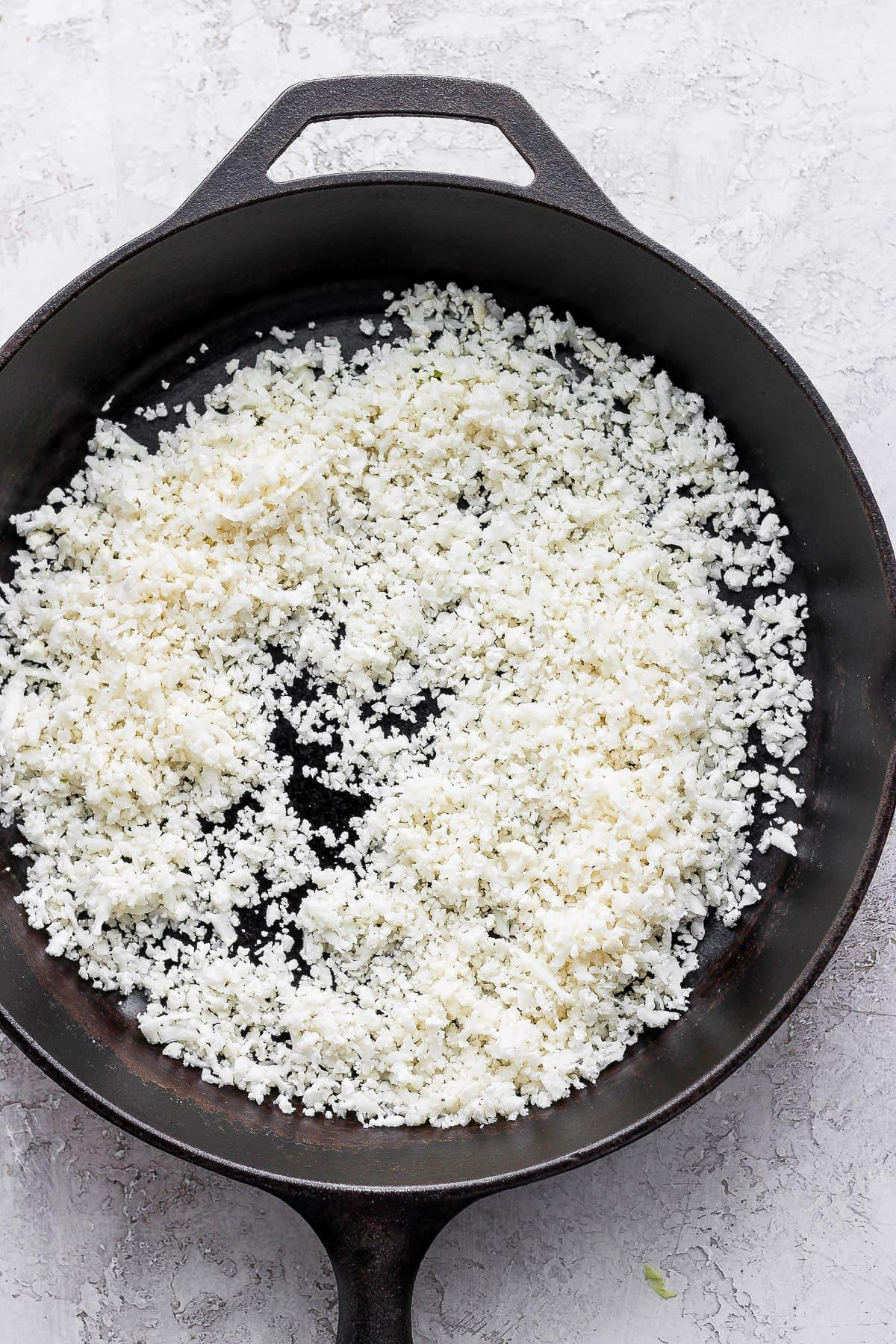 Cauliflower rice in a cast iron skillet.