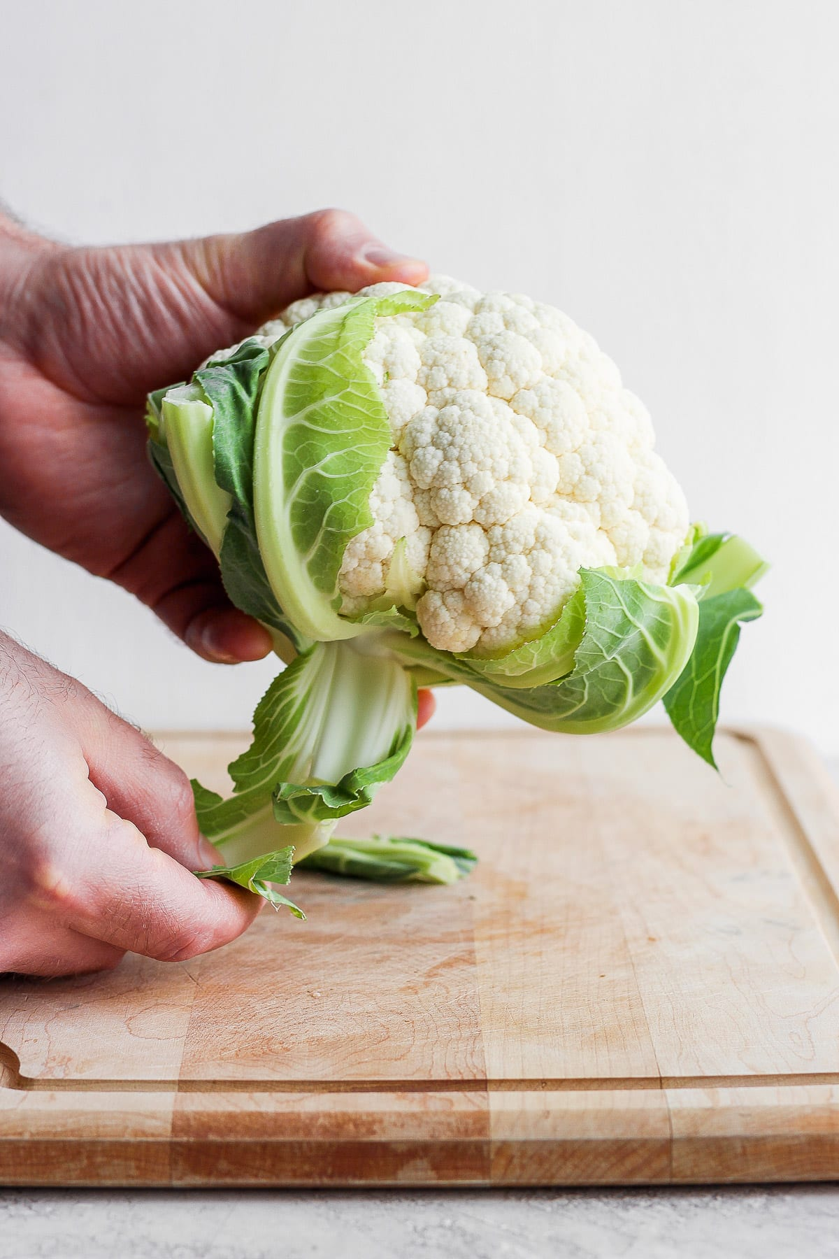 Someone removing the leaves from a head of cauliflower.