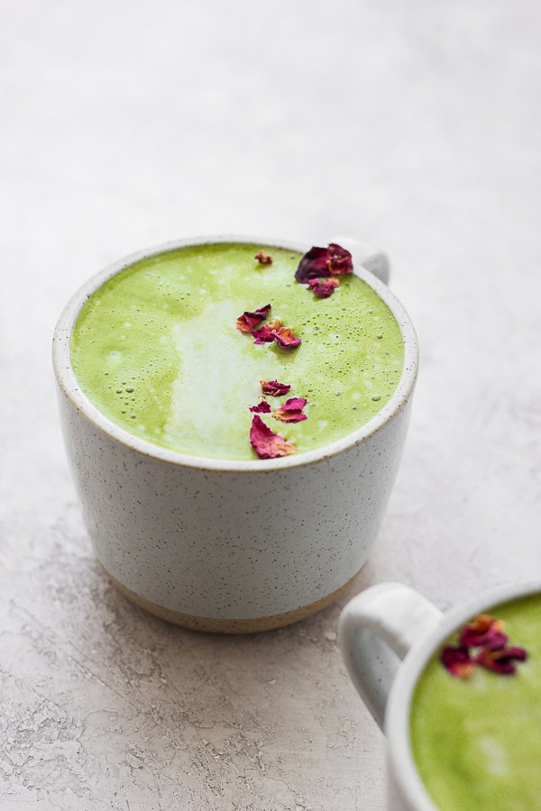 Matcha latte in a mug with some dried rose petals sprinkled on top.